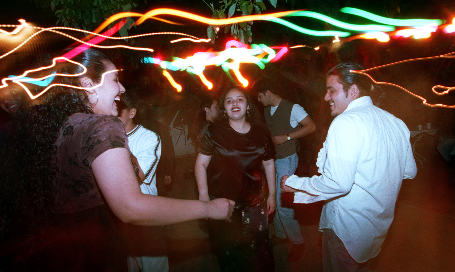 Araceli, left, with friends and family dance the night away in Santa Ana at a cousin's first communion party. ©Gail Fisher Los Angeles Times