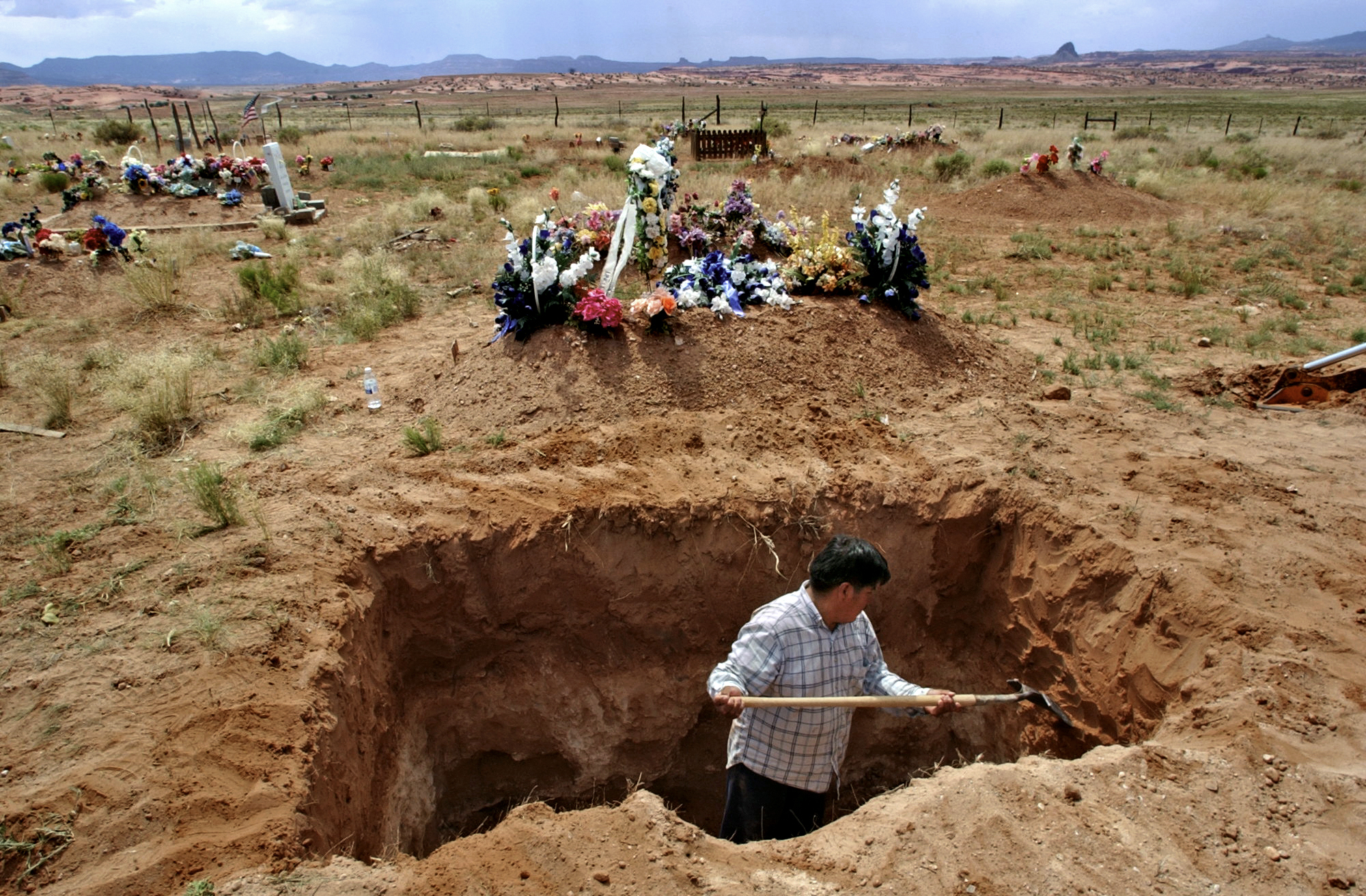 Albert Jackson digs a grave for his stepfather, Emerson Litson, a former miner in Red Valley who, like many other Navajo miners, died of lung disease. ©Gail Fisher Los Angeles Times