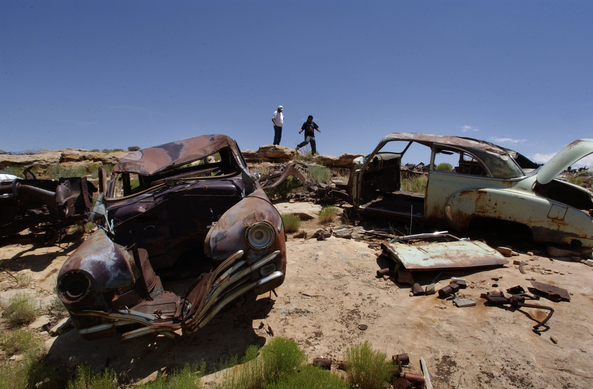 Old cars and contaminated debris lie near the abandoned uranium mining site in the Navajos' Cane Valley, near the Arizona-Utah line. ©Gail Fisher Los Angeles Times