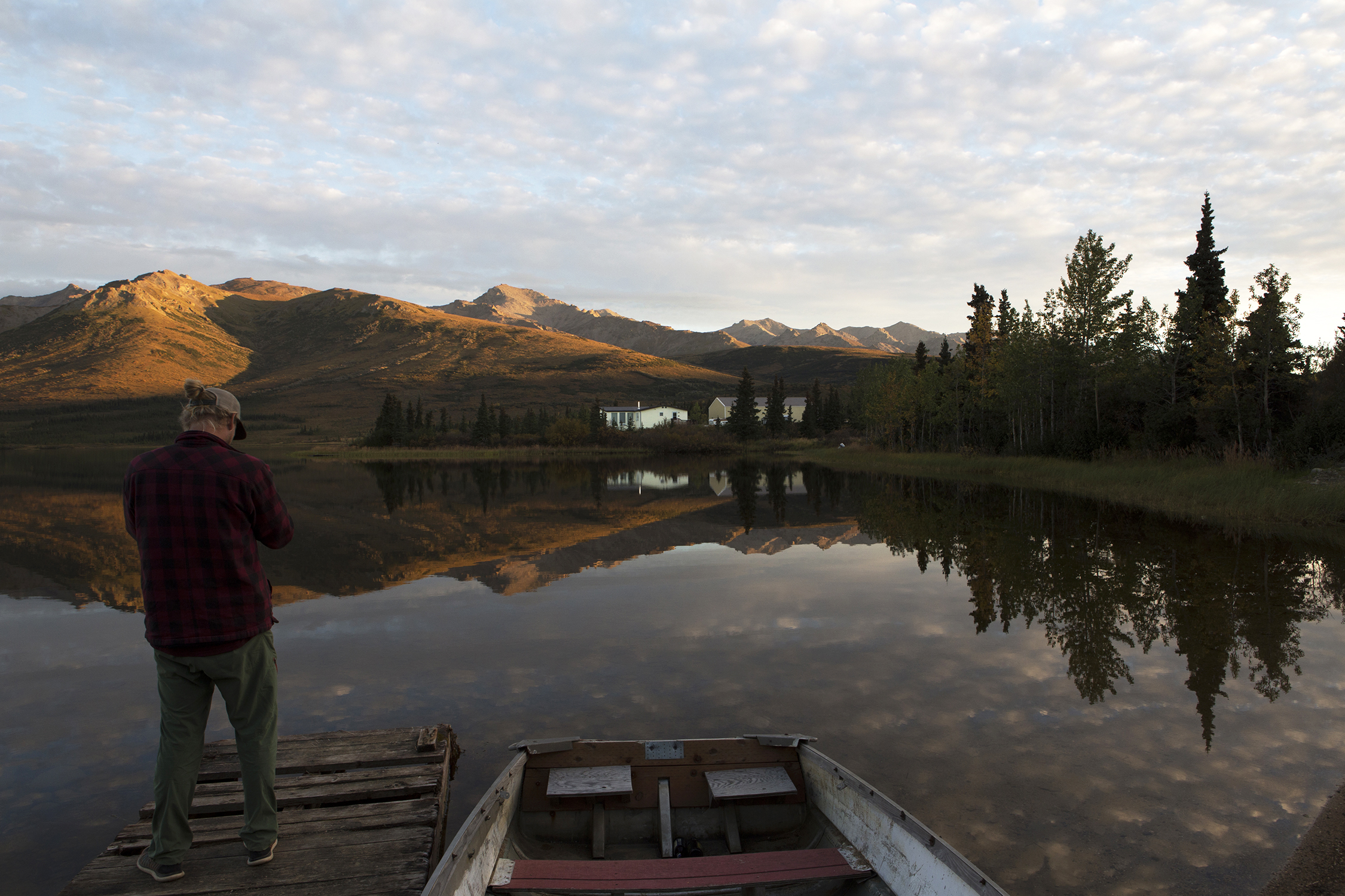 Zachary Patton from southern California, working in Healy, Alaska, enjoys the beauty of the late evening setting sun as it turns the surrounding hillsides a golden hue over Otto Lake. © Photo by Gail Fisher
