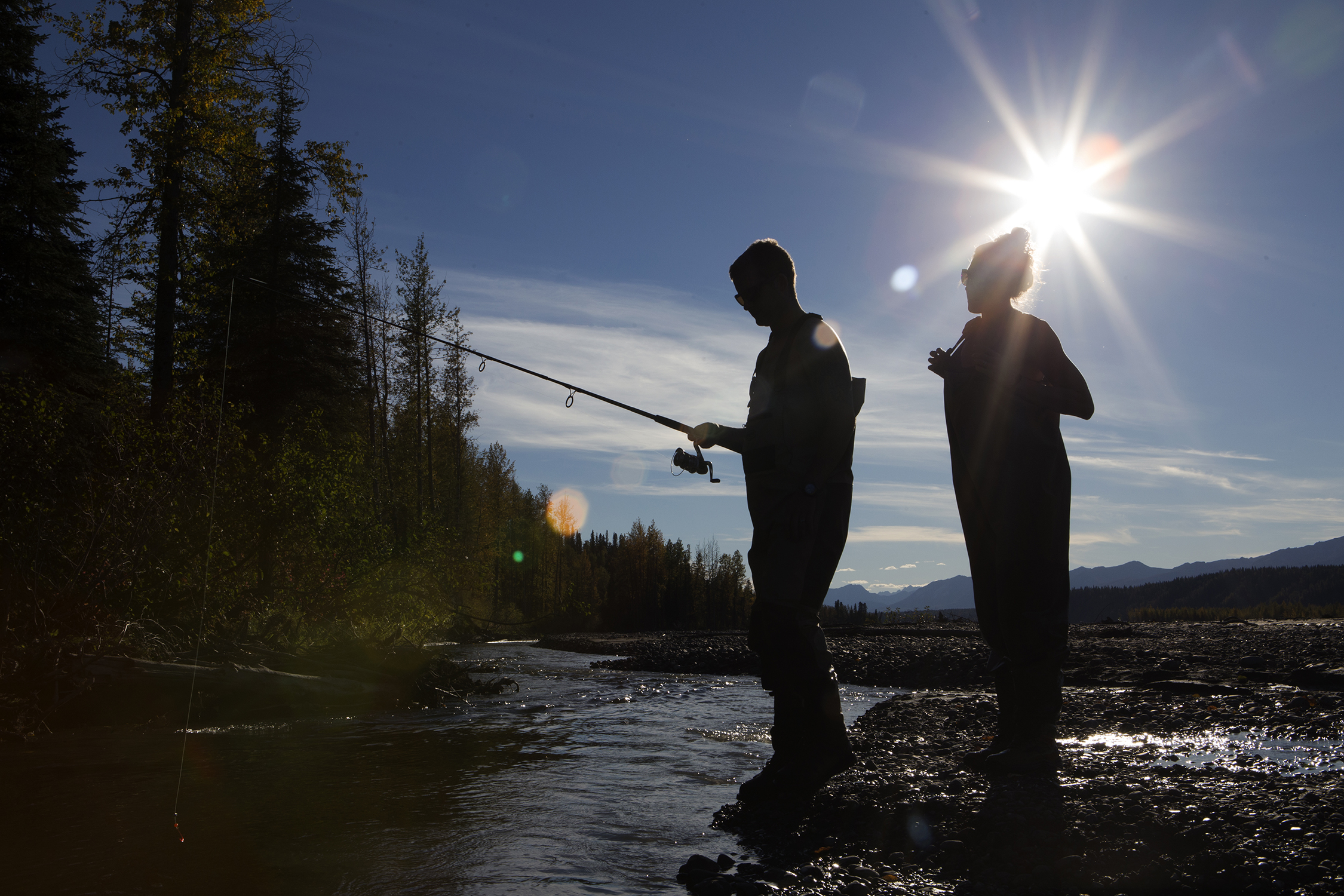 Austin and Whitney Krempin from southern California enjoy an afternoon in autumn fishing while wading through glacial streams outside Talkeetna, Alaska. © Photo by Gail Fisher