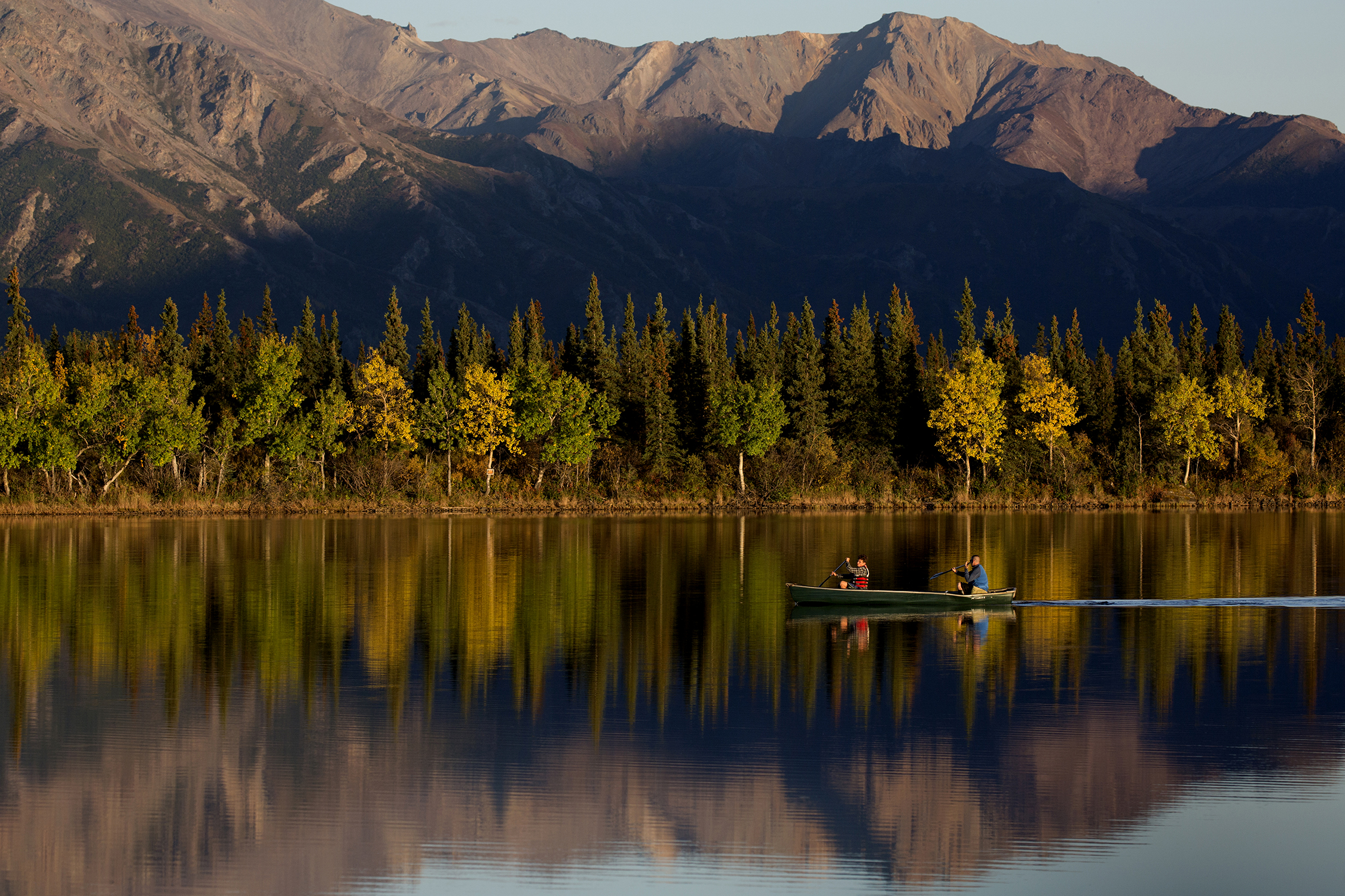 Kayakers glide over calm mirror-like Otto Lake with autumn turning leaves into a yellow hue, located a couple miles outside Healy, Alaska.  © Photo by Gail Fisher