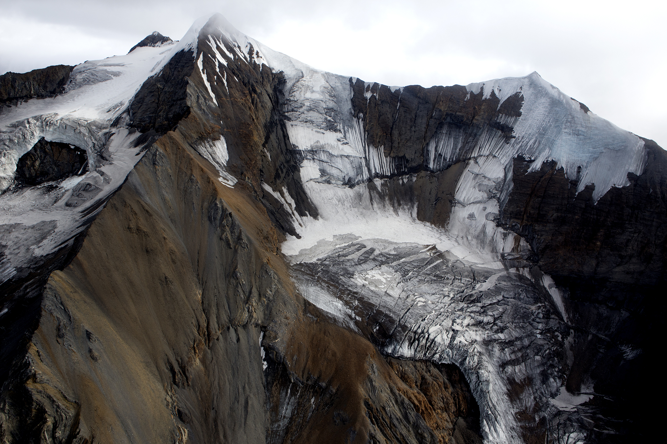 Large amounts of rock debris are carried on, in, and beneath the ice as the glaciers move downslope in the Alaska Range. © Photo by Gail Fisher