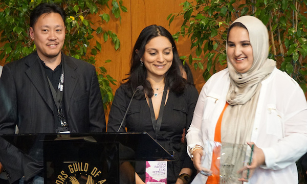 """AS EXECUTIVE PRODUCER ALAN PAO AND PRODUCER MEGHA KADAKIA LOOK ON, DIRECTOR/CO-SCREENWRITER LENA KHAN ACCEPTS THE FESTIVAL GRAND JURY PRIZE FOR HER DEBUT FEATURE NARRATIVE """"THE TIGER HUNTER"""" IN CEREMONIES PRECEDING FESTIVAL CLOSING NIGHT ON APRIL 28. (PHOTO: STEVEN LAM)"""