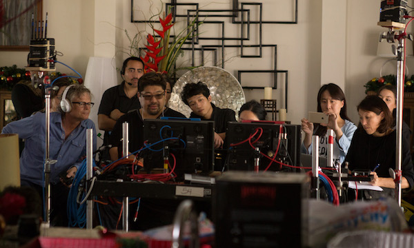 """DIRECTOR JONATHAN LIM (THIRD FROM LEFT, WEARING GLASSES) REVIEWS A TAKE WITH MEMBERS OF THE CREW DURING THE MAKING OF """"PALI ROAD,"""" THE FILM FESTIVAL'S CLOSING NIGHT PRESENTATION. (PHOTO: COURTESY THE FILMMAKER)"""