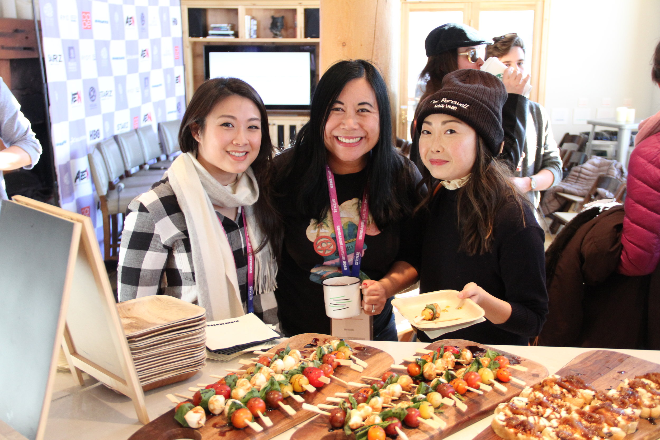 As the Kickstarter Lodge begins to fill up for a full afternoon program of panels and party, Producers Guild of America member Christina Lee Storm is greeted by Vivian Lin of Netflix (left) and filmmaker Lulu Wang (THE FAREWELL) (Photo: Abraham Ferrer/Visual Communications Photographic Archive)