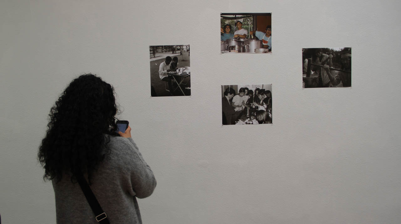 On of many guests at the April 5 Opening Night of CENTERING THE MASSES takes in images curated by Yuri Shimoda's exhibit OUT OF THE SHADOWS: BUILDING COMMUNITIES THROUGH THE ARTS. (Photo: Abraham Ferrer/Visual Communications Photographic Archive)