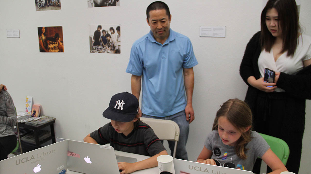 Video games developer Randall Fujimoto and assistant check in on participants during the interactive workshop BUILDING HISTORY 3.0 at 341FSN. (Photo: Abraham Ferrer/Visual Communications Photographic Archive)