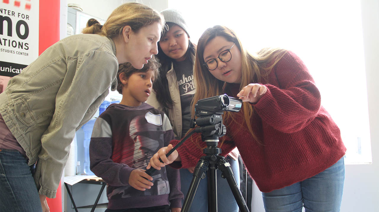 A budding documentary filmmaker receives some much-welcome instruction during a camera exercise as part of the CREATING COMMUNITY MEDIA BOOT CAMP at 341FSN. (Photo: Abraham Ferrer/Visual Communications Photographic Archive)