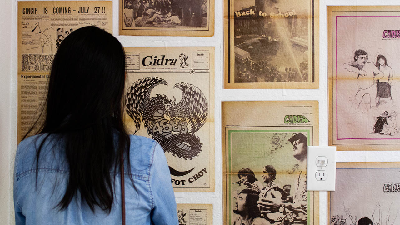 "A visitor to ""centering the masses"" views the gidra ""wall of tribute"" at 341fsn. (photo: Josaen Ronquillo/visual communications photographic archive)"