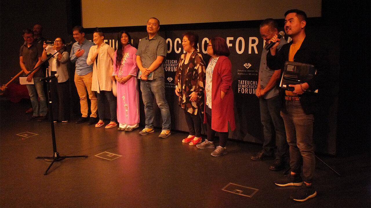 "Host Sean Miura (far right): congratulates the artists whose works informed the ""At First Light"" program ""Reflections/Refractions: 10 Works Inspired by ""At First Light"" at the Tateuchi Democracy Forum (from left): Eric C. Wat, Dom Magwili, Irene Suico Soriano, Stan Yogi, Traci Kato-Kiriyama, Teresa Mei Chuc, Kenji Liu, Miya Iwataki, Naomi Hirahara, and Taiji Miyagawa. (Photo: Florante Ibanez/Visual Communications Photographic Archive)"