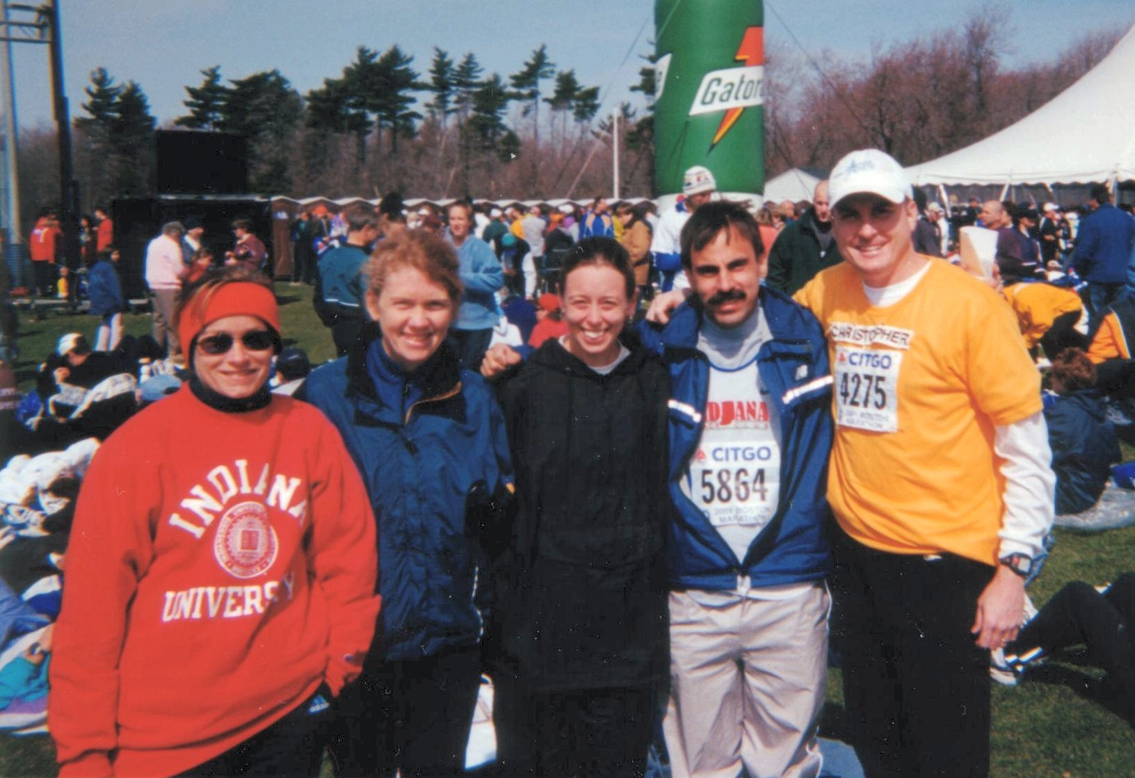 Runners Jill Boerigter, Linda Branstetter, Heather May, Bob Andree, and Christopher Goss (from left) huddle up at the athlete's  village in Hopkinton, MA on the morning of the 2001 Boston Marathon.