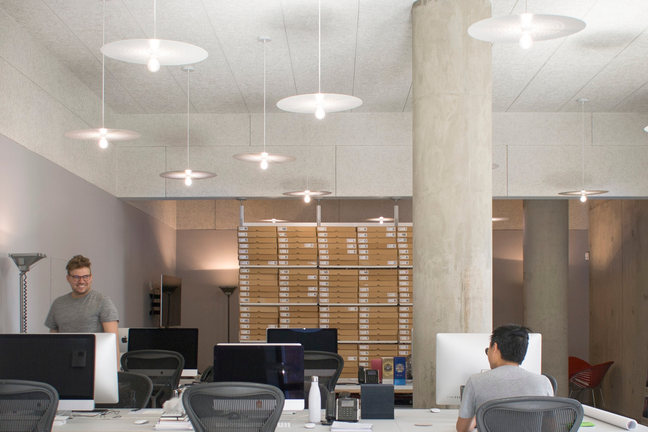 White Circular Superlight Pendants Suspended from Ceiling in Office
