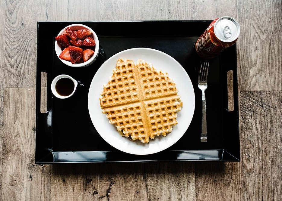 sour cream waffles on a bed tray with strawberries, syrup and soda