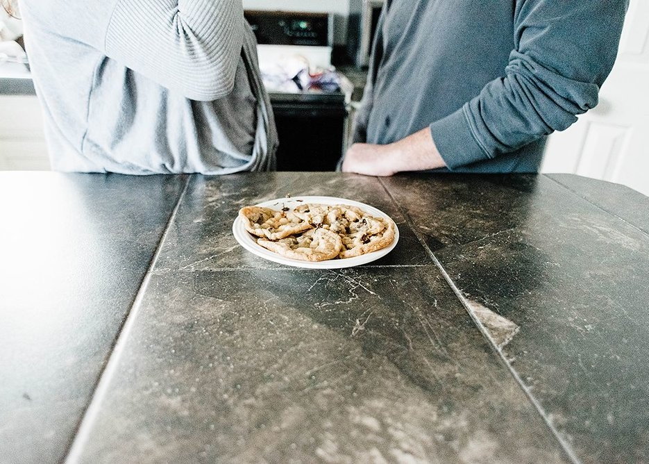 plate of chocolate chip cookies on counter in front of couple