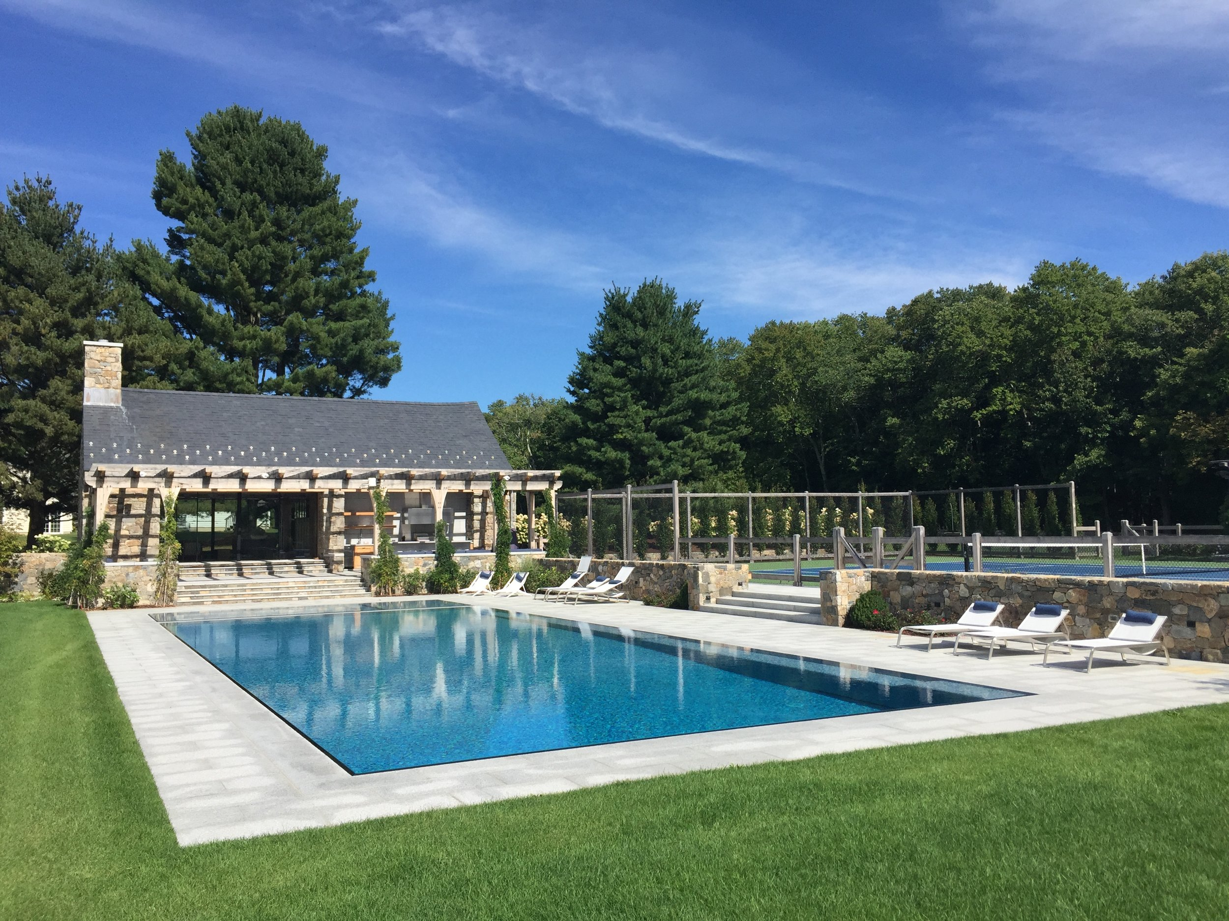 An adjacent tennis court's size and proportions were used to trigger the design of the pool and spa. Both watershapes feature knife-edge-slot, perimeter-overflow designs that give them the appearance of floating above the surrounding deck.