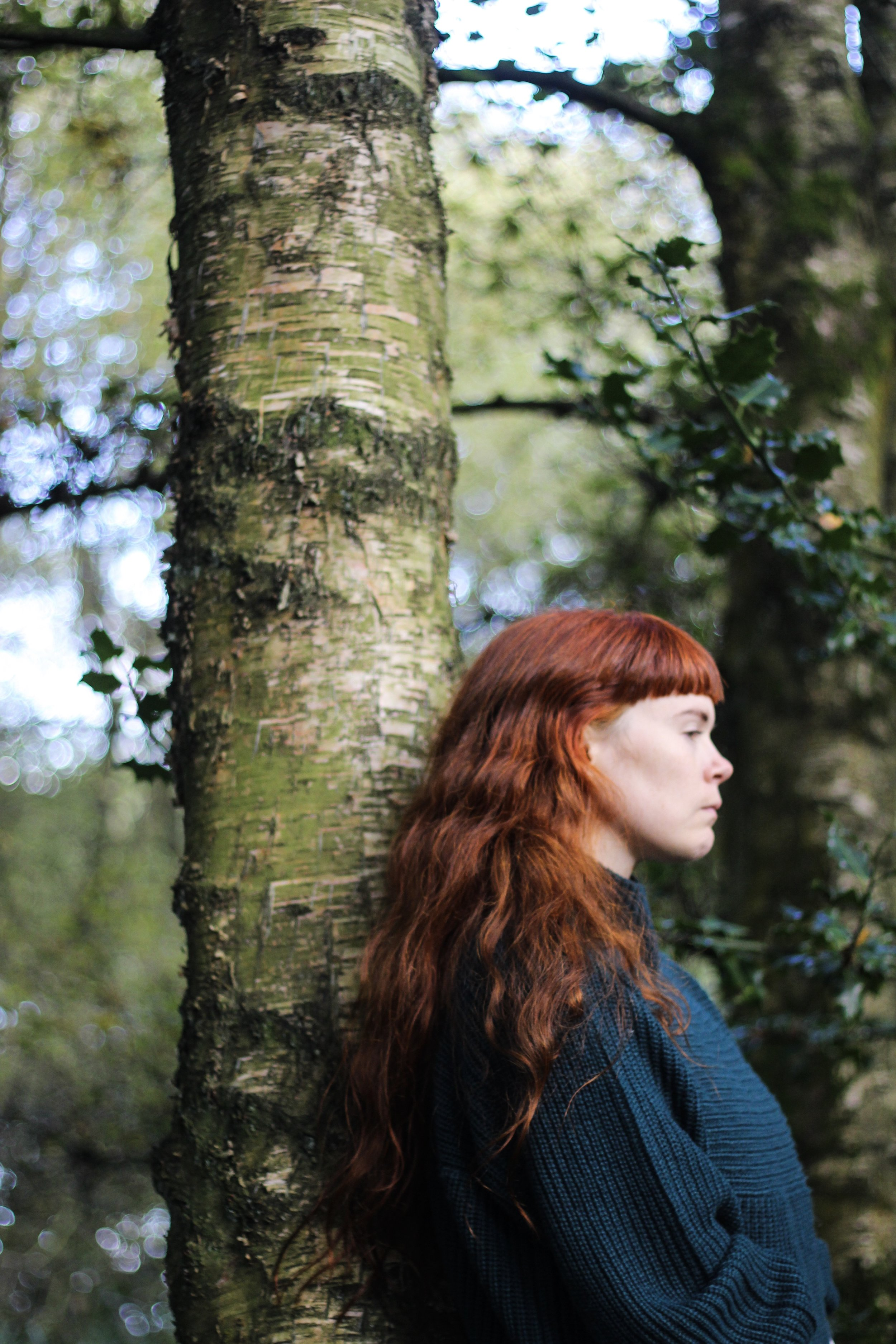 Girl with red hair in woods