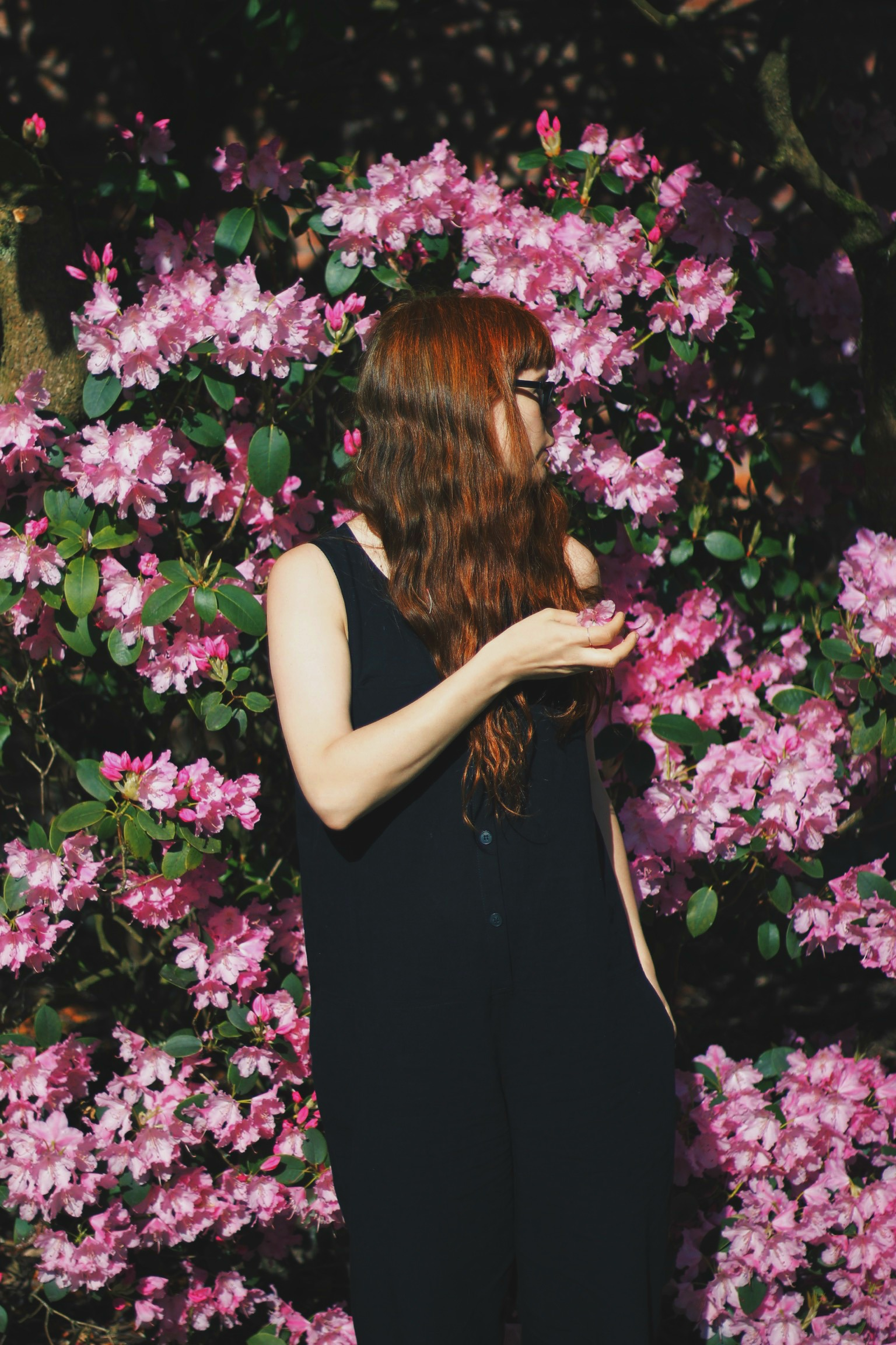 girl standing in front of floral bush