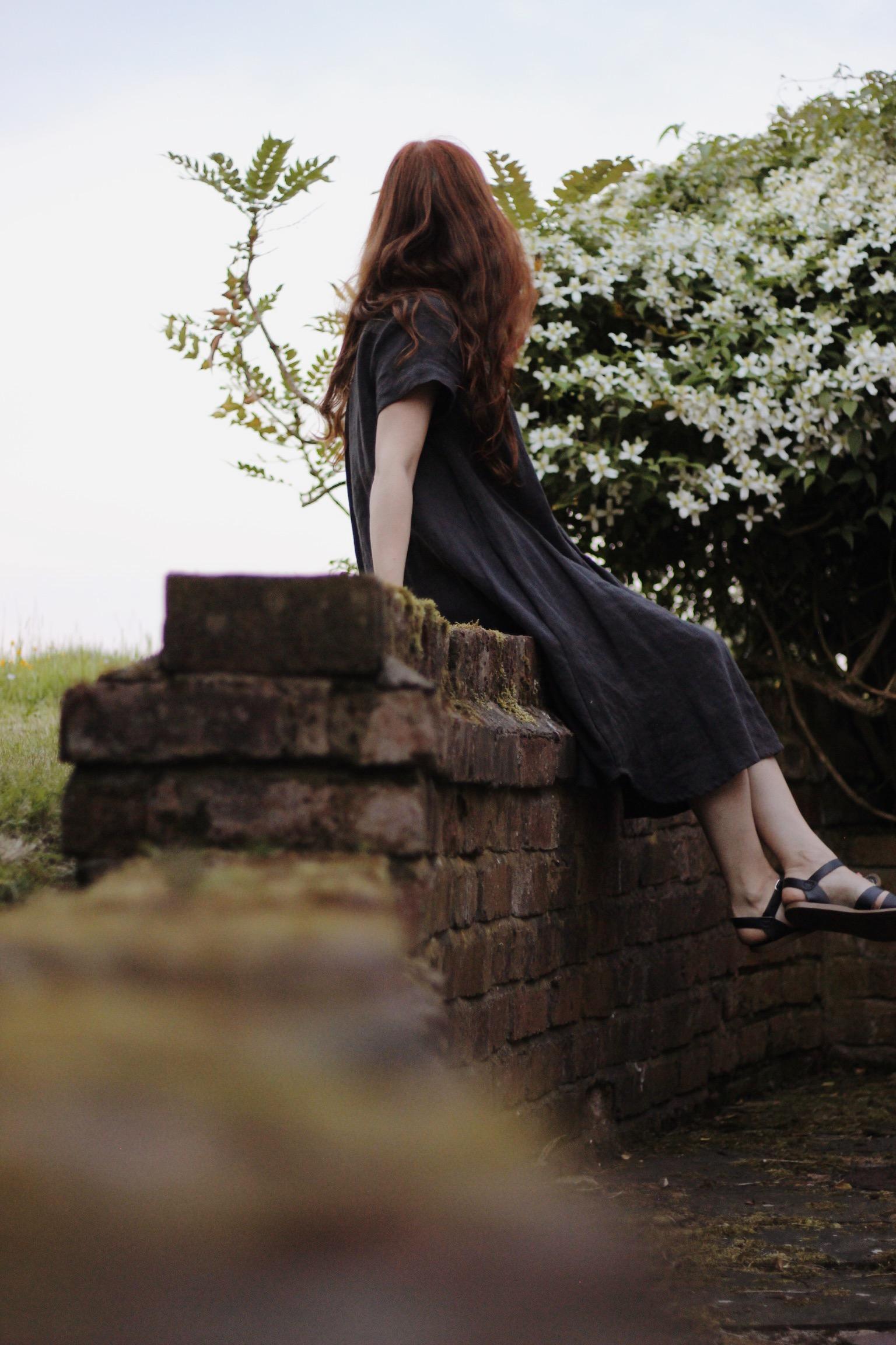 Girl wearing linen Toast dress sat on wall