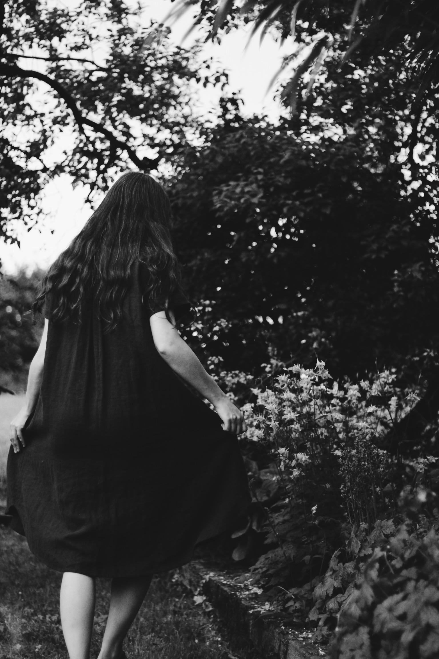 Girl walking through flower bushes
