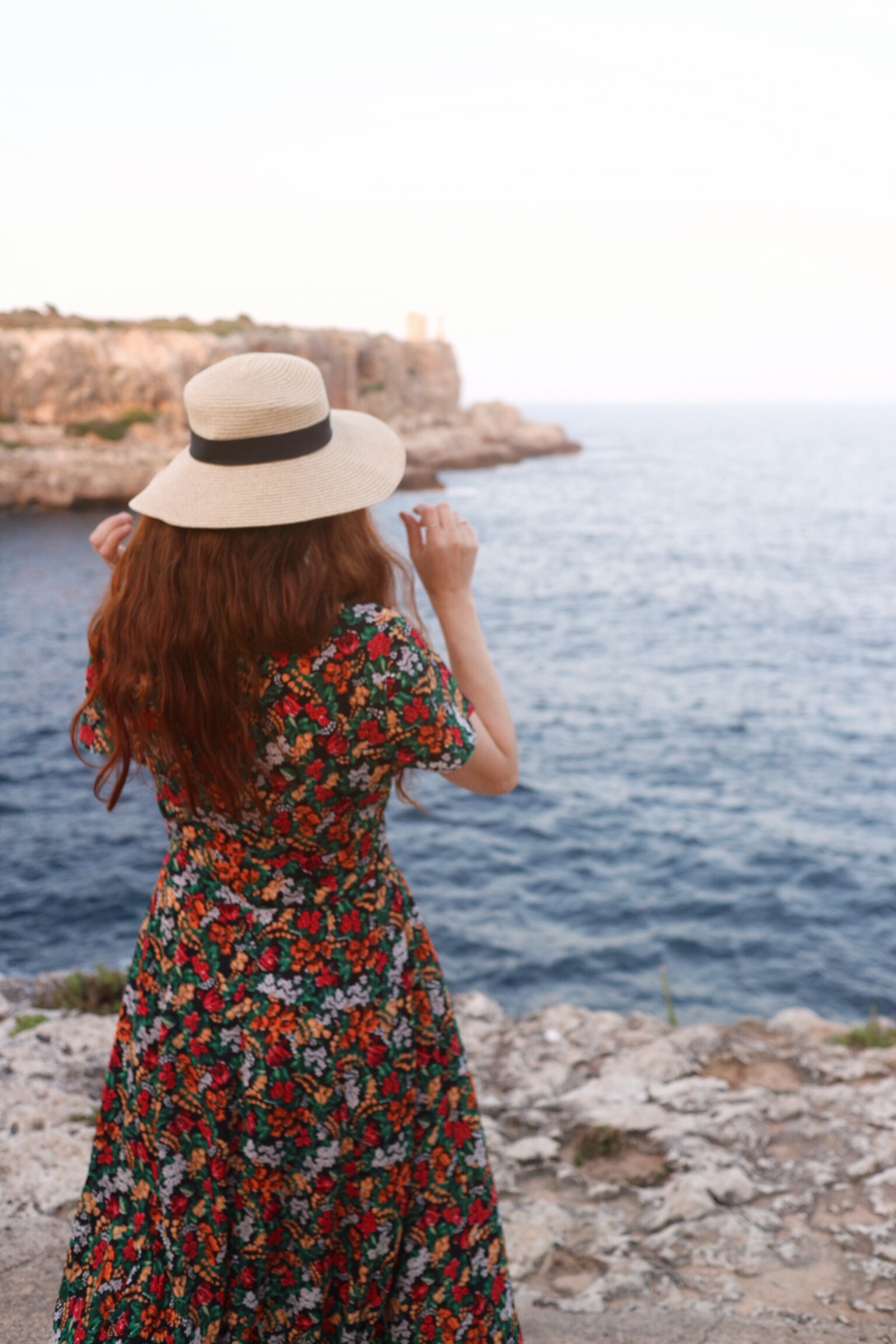 Girl on cliff in hat