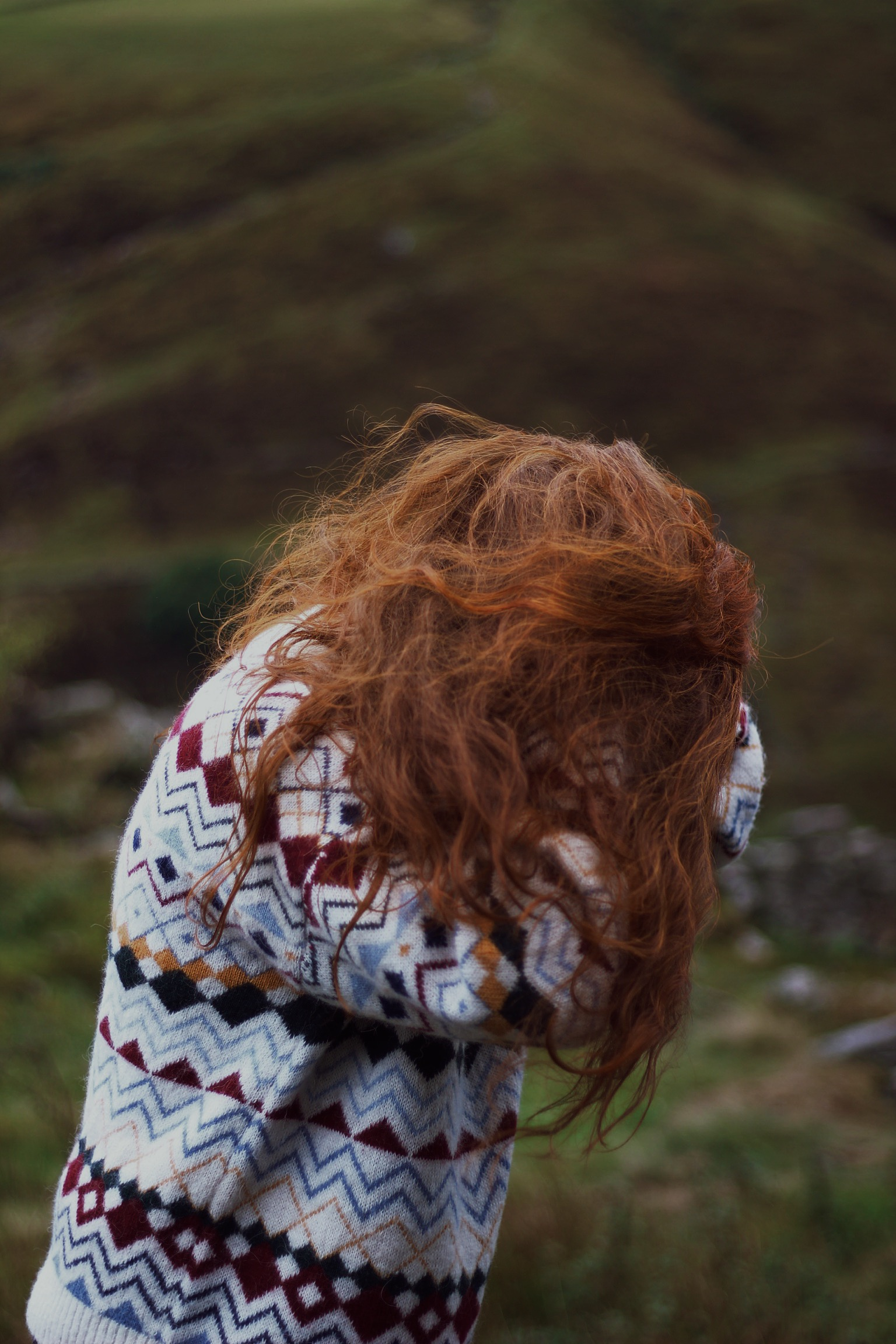 Red haired girl shaking hair in wind