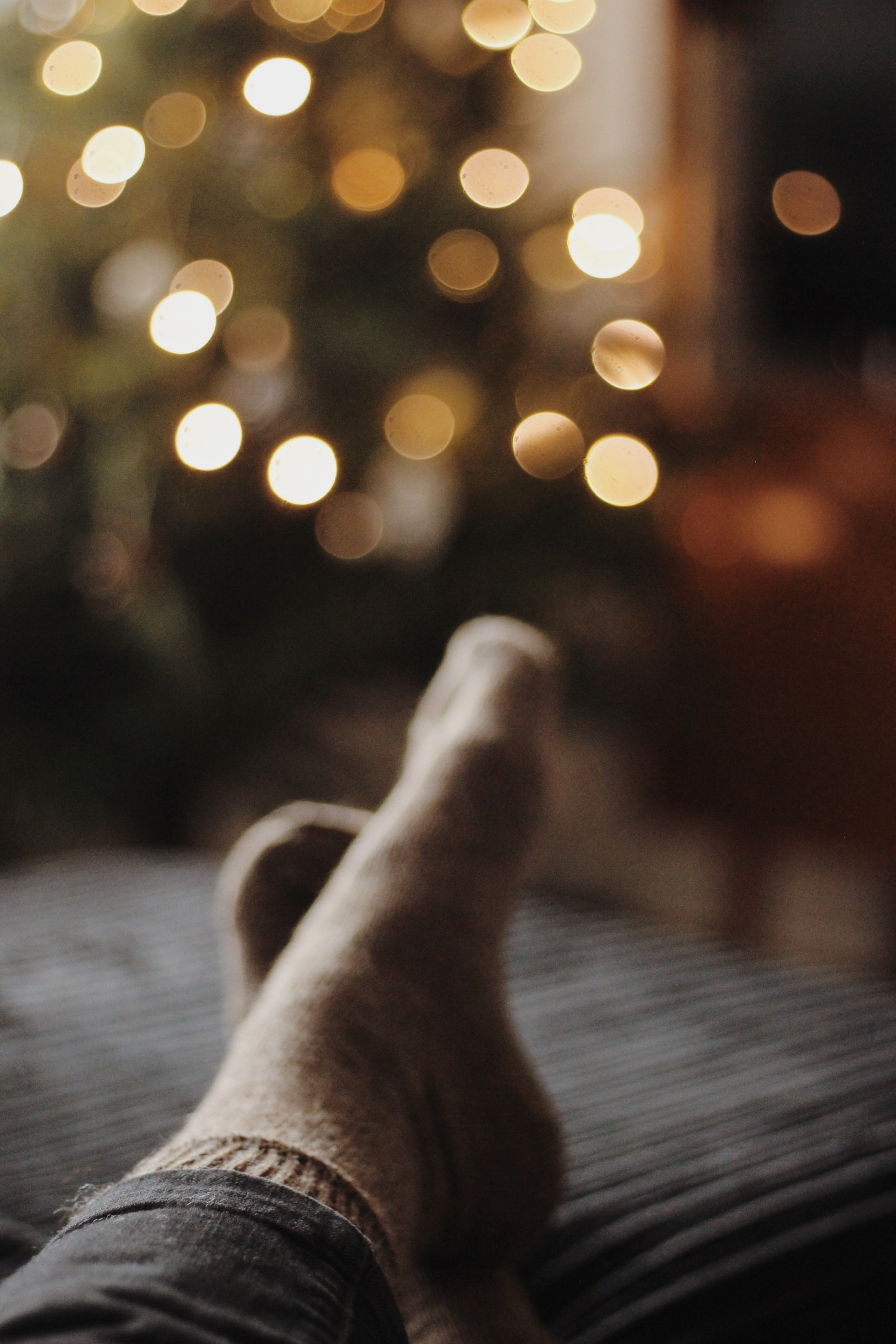 Cosy Christmas, warm woolly socks, bokeh Christmas tree lights