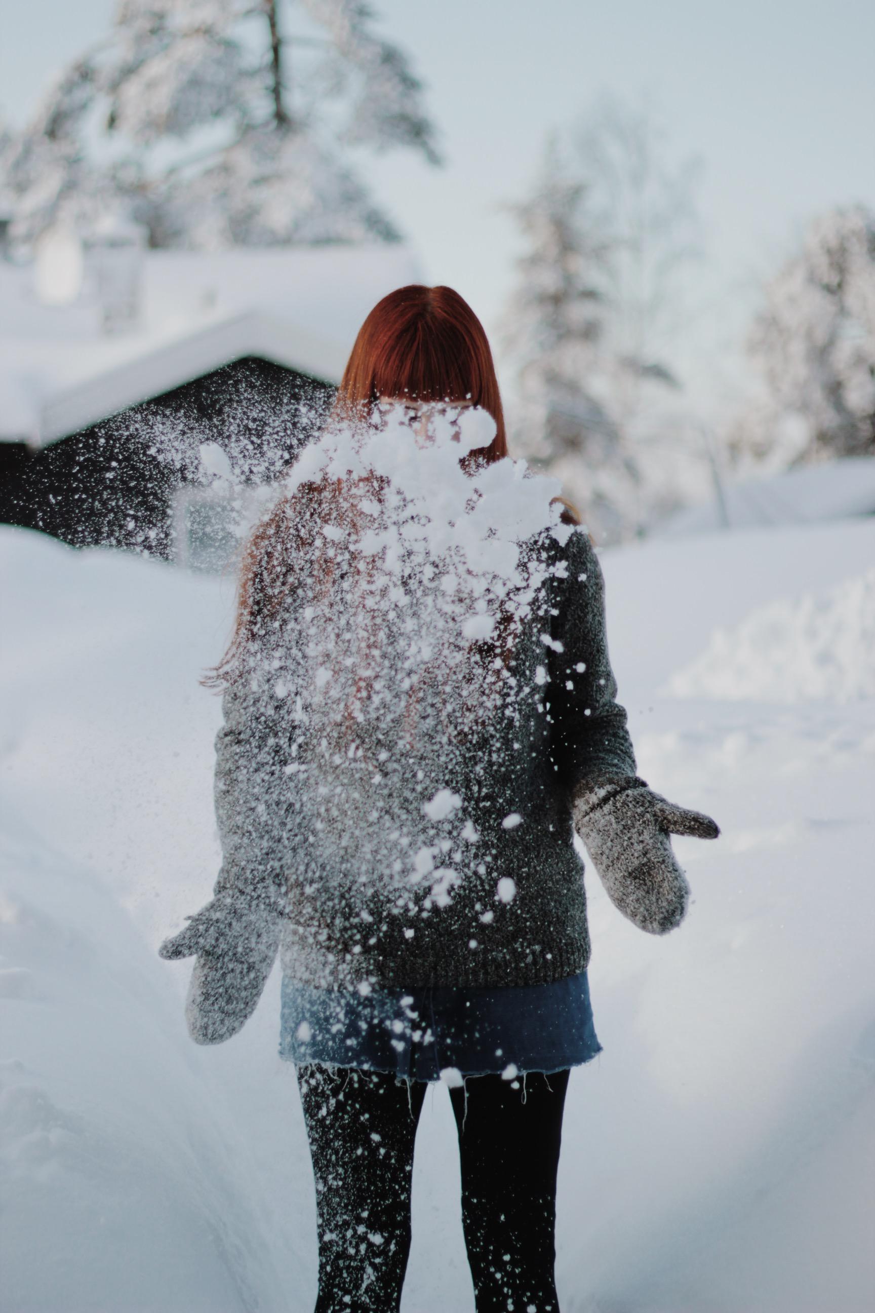 Girl throwing snow in air, Oslo, Norway