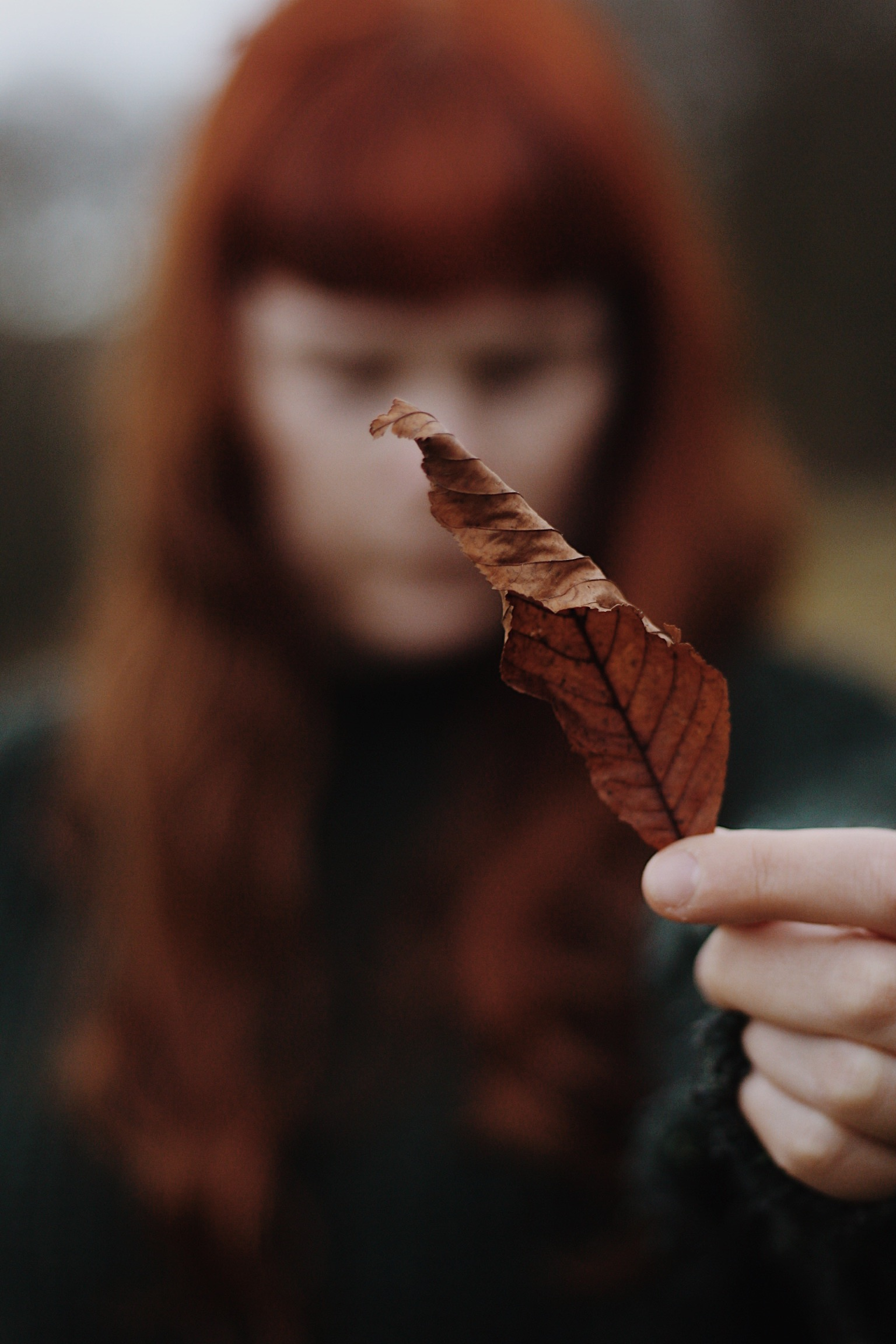 Red haired girl holding leaf
