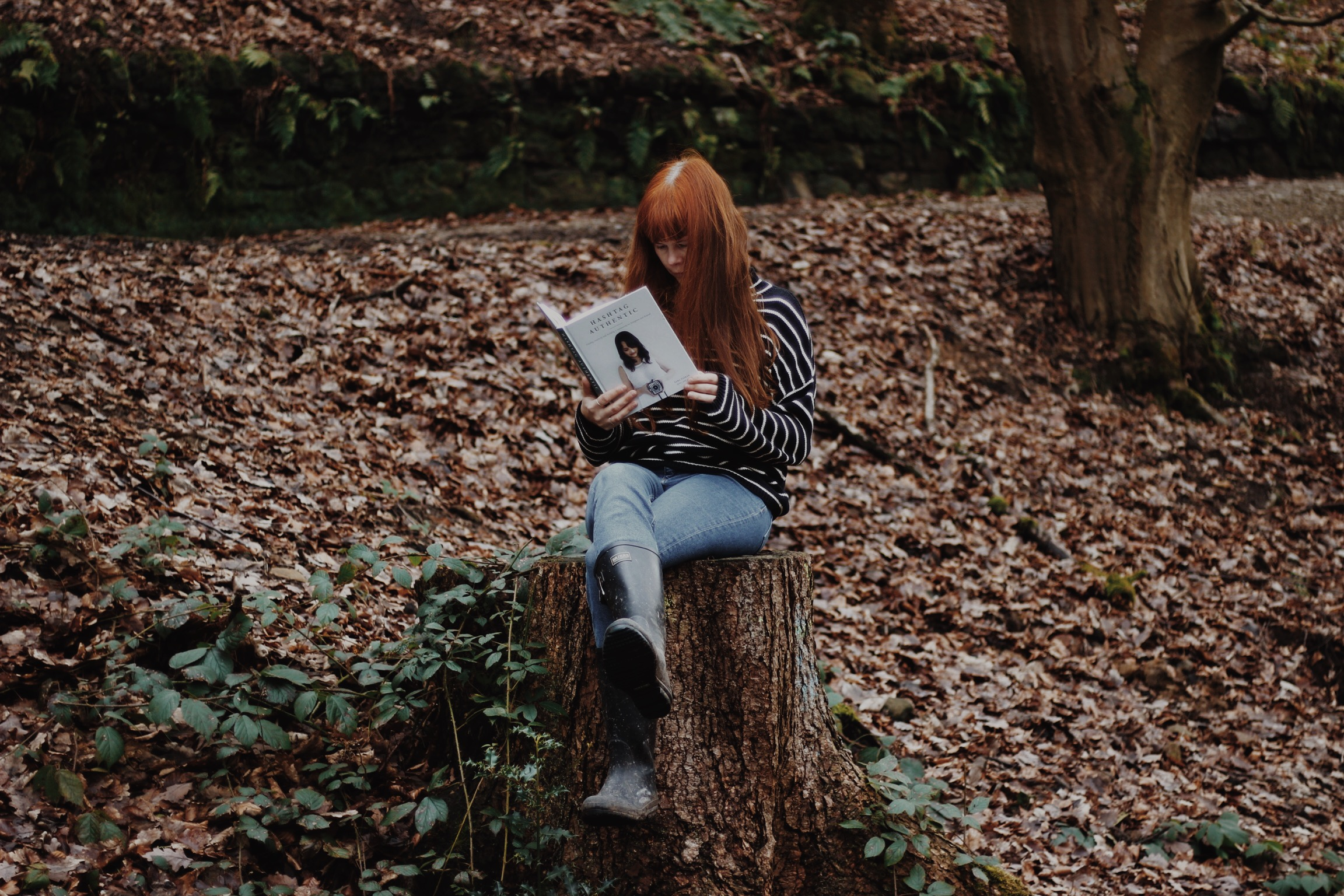 Girl reading a book in the woods