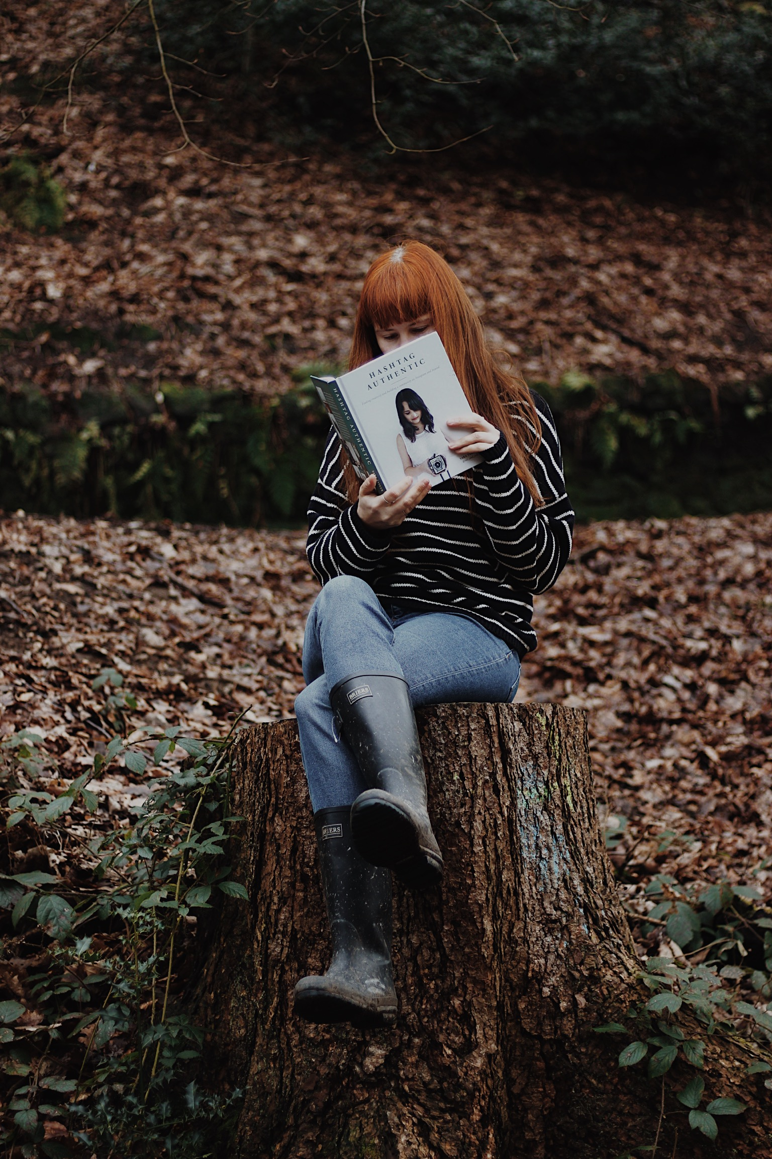 Girl reading book in woods