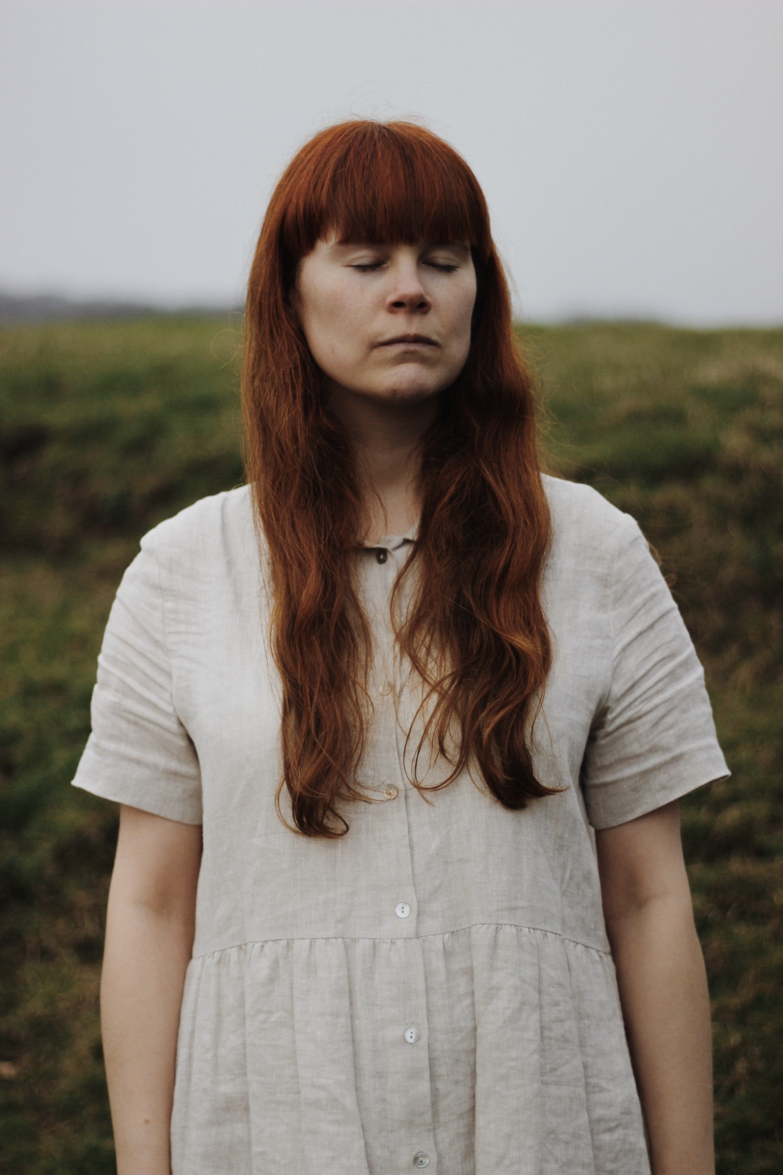 Red haired girl in a linen dress