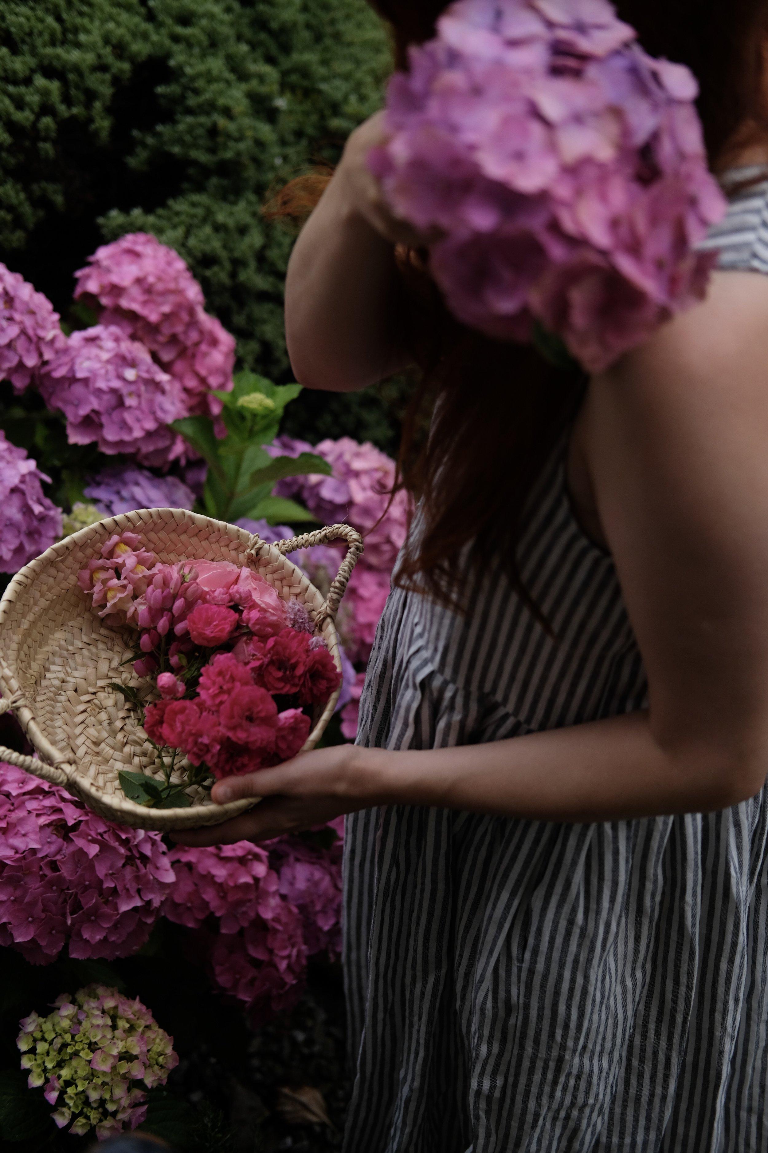 Girl holding basket of pink flowers | Field + Nest