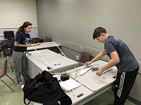 During Discovery term, the students designed a safe, portable, low-cost, innovative device that could be made from simple materials to empower an amputee to put on pants and a shirt entirely on their own.