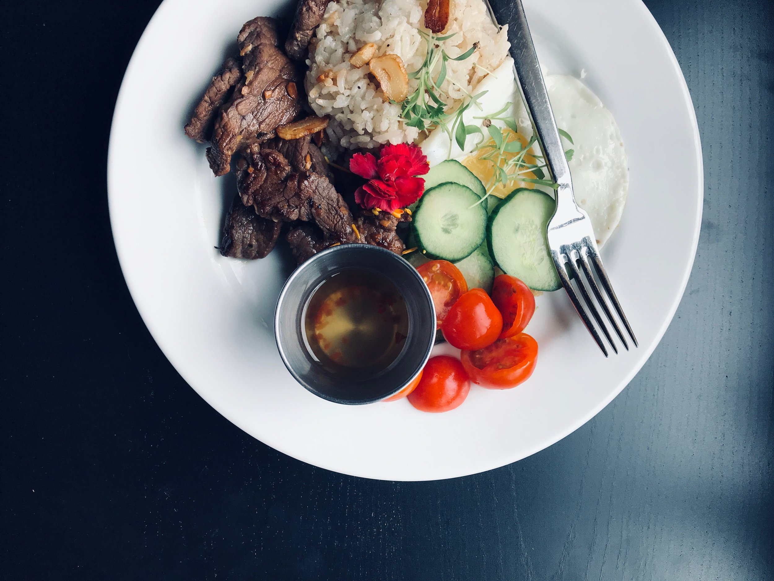 Tapsilog, Filipino tapa sirloin steak, fried chicken egg, fresh cucumber and cherry tomatoes with garlic fried rice. A new spring dish!