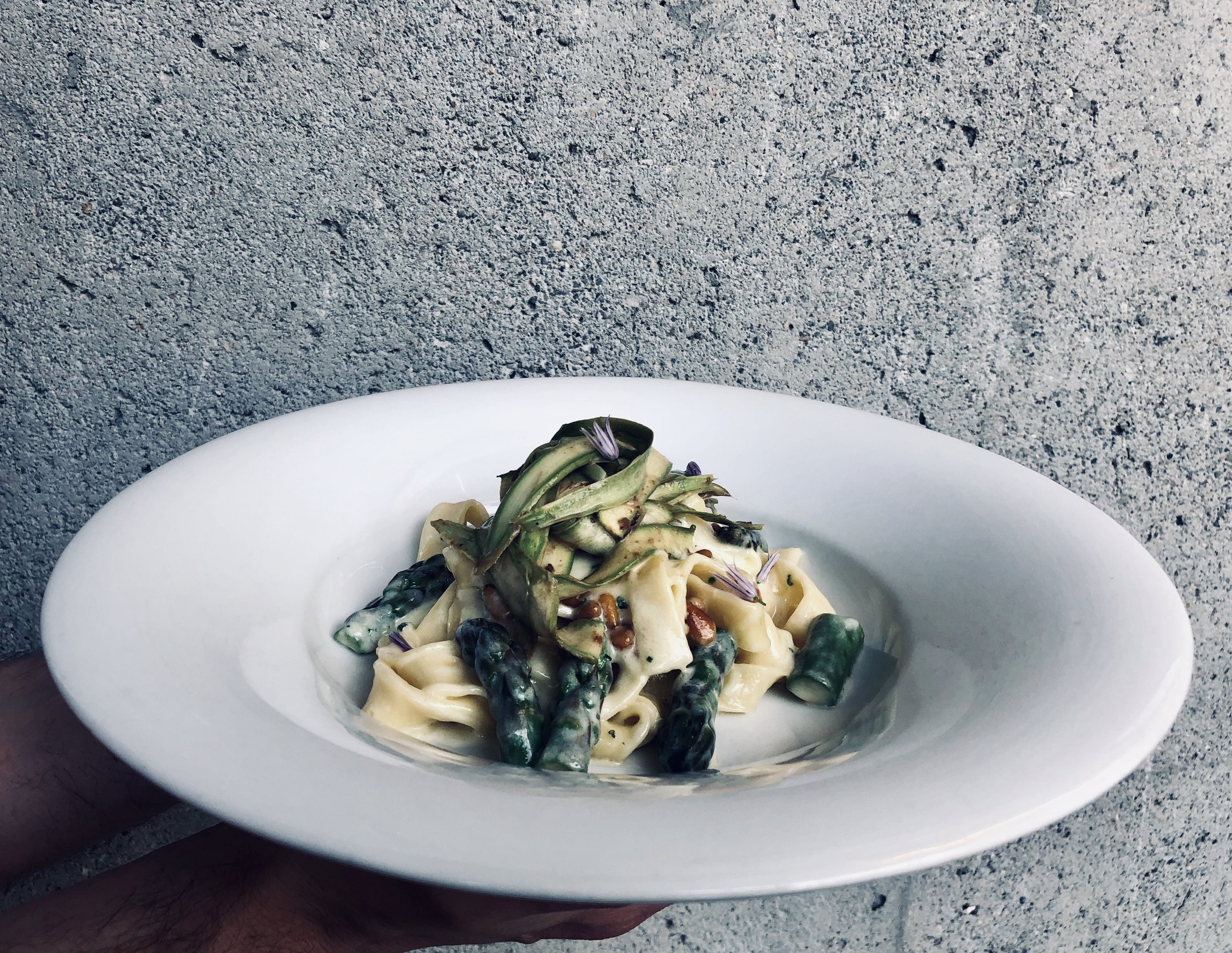 Tagliatelle with asparagus, pine nut butter sauce, black garlic, and pecorino.