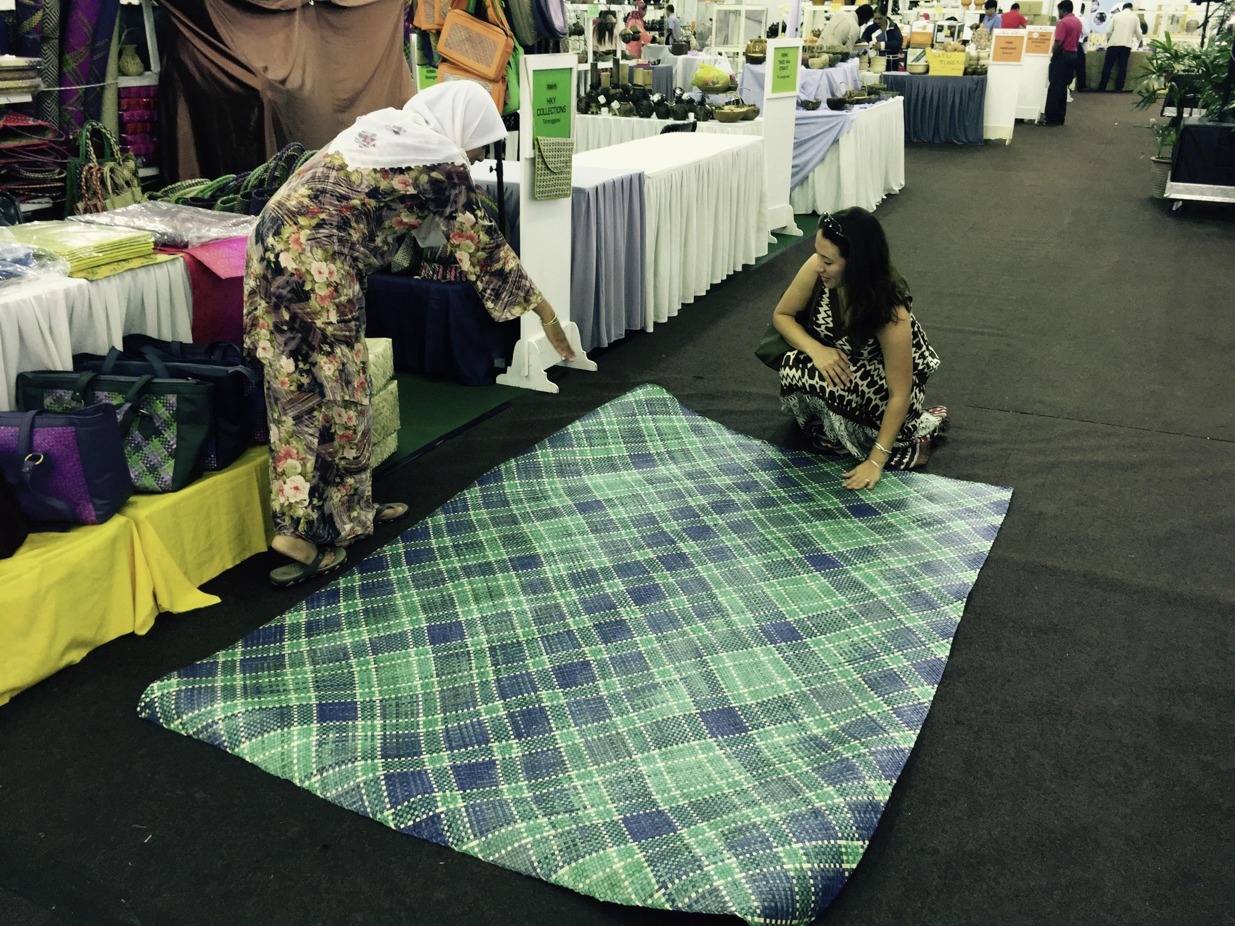 Yiga admiring this beautiful handwoven green and blue rattan floor mat from Terengganu, Malaysia.