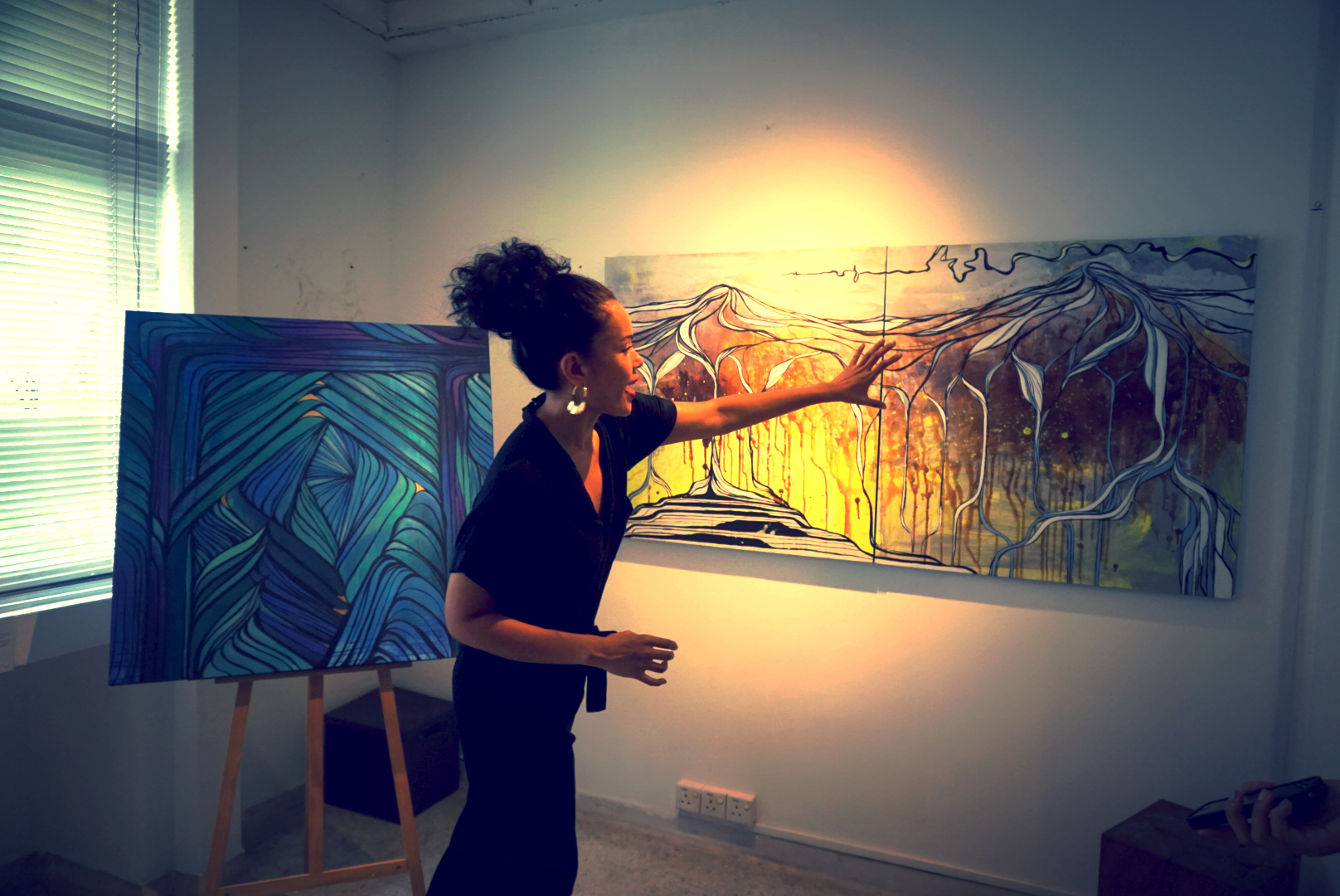 """Nini describing her vision behind her painting, """"Iceland: Weaving Iceland"""". Behind her lies one of Nini's personal favourites,Enchanted Door"""
