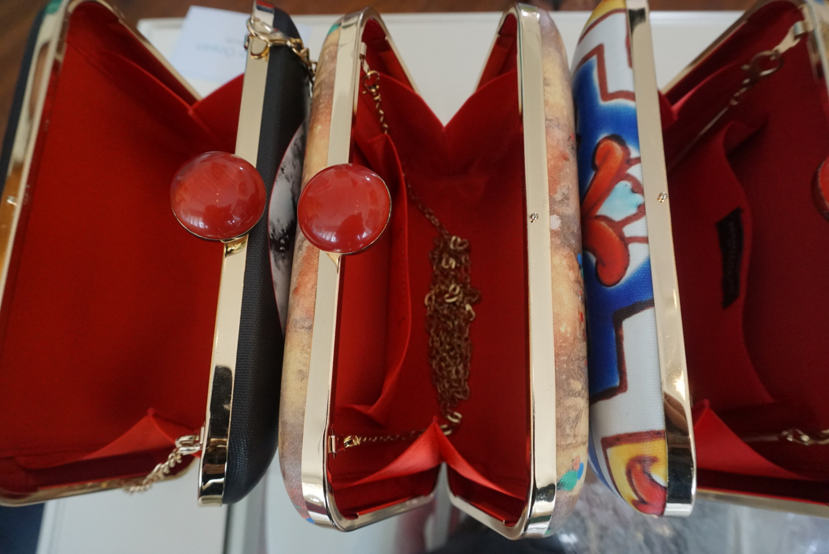 Beautiful red silk interiors paired with coloured clasps adorn each clutch at Indian Ocean by Shailly