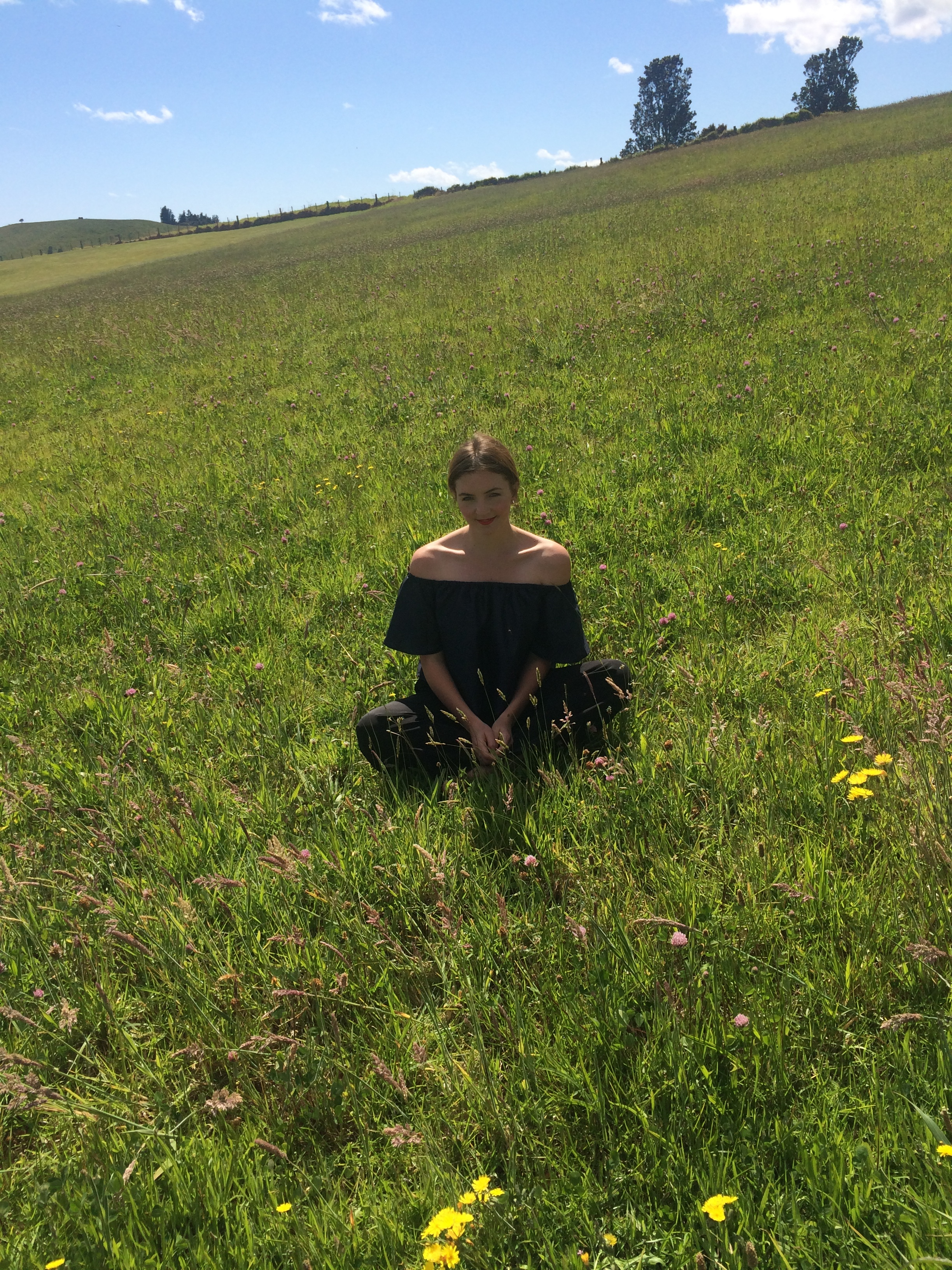 Woman sitting in a large green field