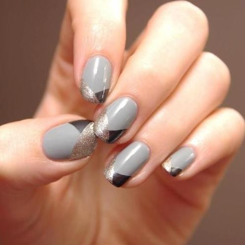hand with grey and gold geometric nail art