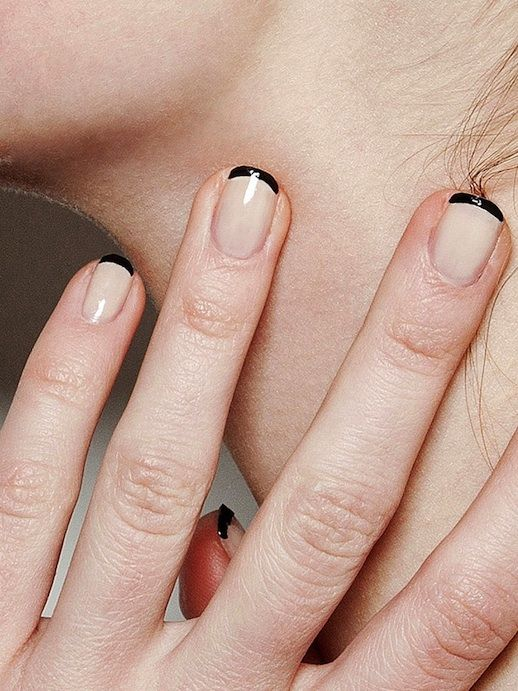 hand with black french tips holding neck