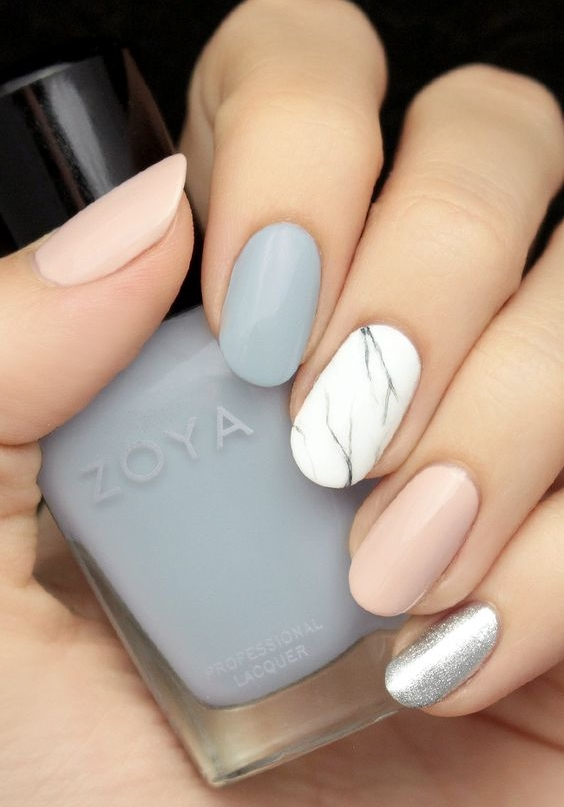 hand with alternating nail colours and patterns like marble holding a blue zoya nail polish