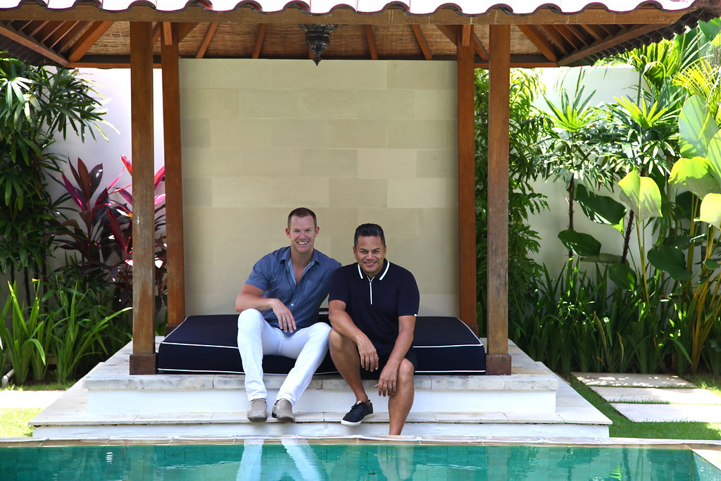 Two men sitting by the pool in a Bali resort