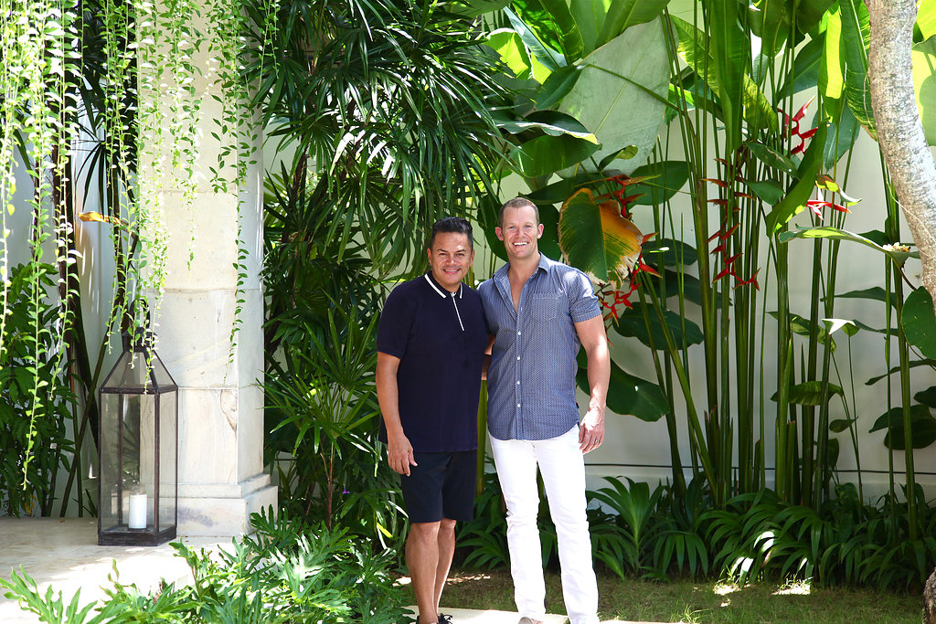Two men standing side by side in a lush leafy area of their villa in Bali