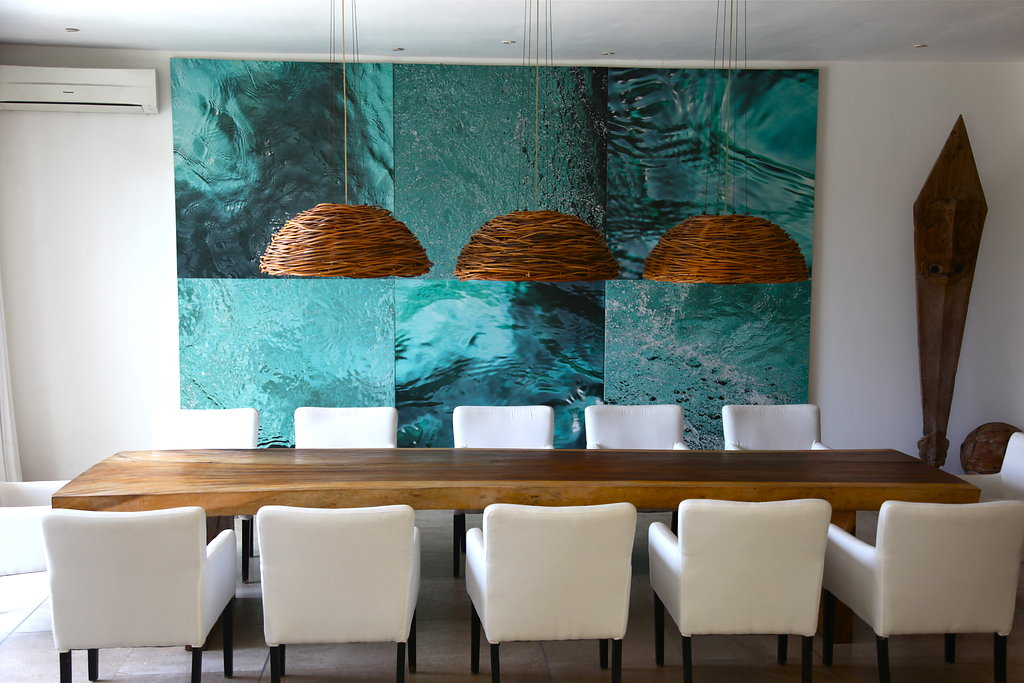 Long wooden table with blue art in on the wall