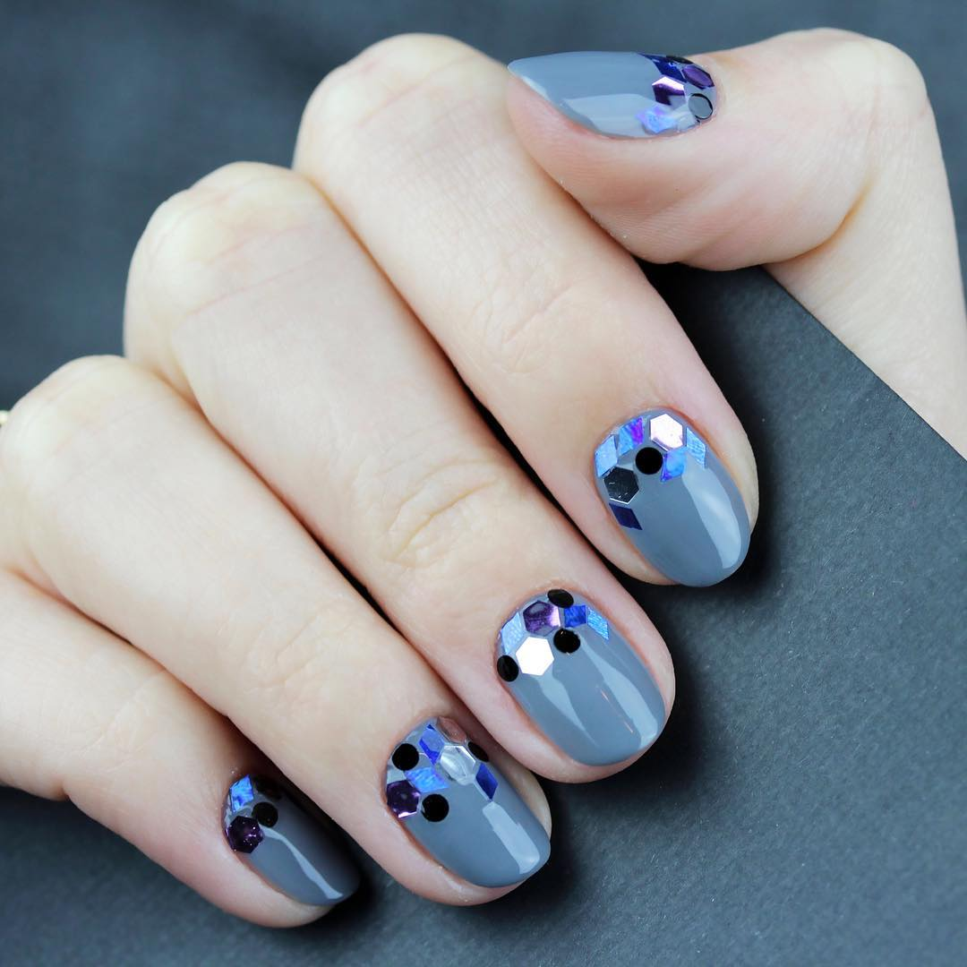 hand with dark blue nails and polka dots holding purse