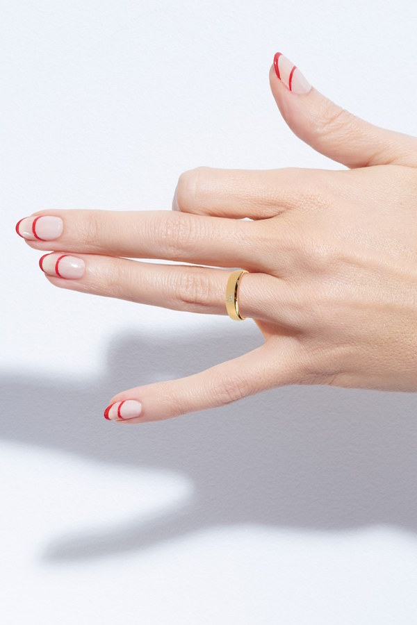 stripe nails with red tips making gun shape with hand