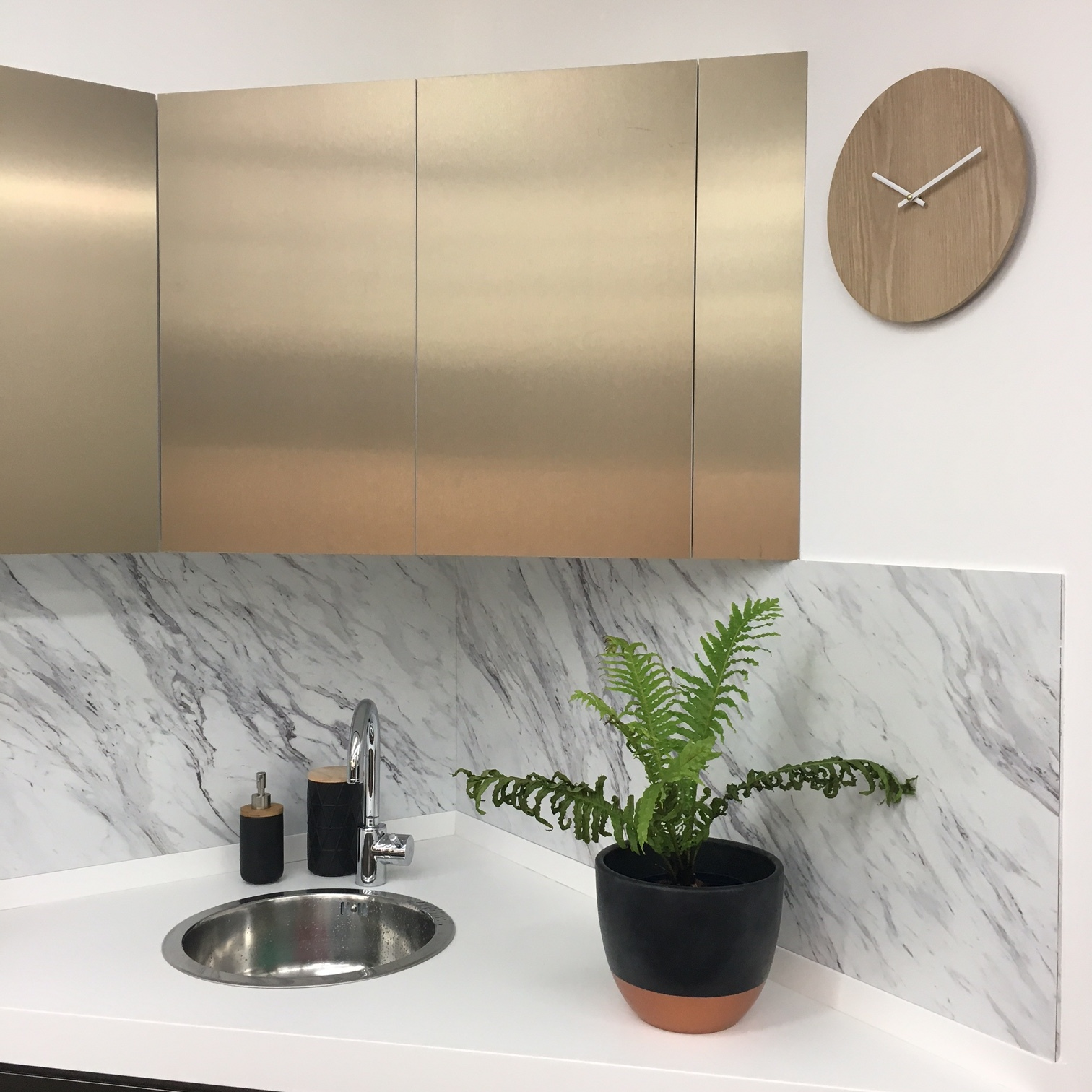Kitchen corner with marble walls, brass cupboards and a plant on the white bench