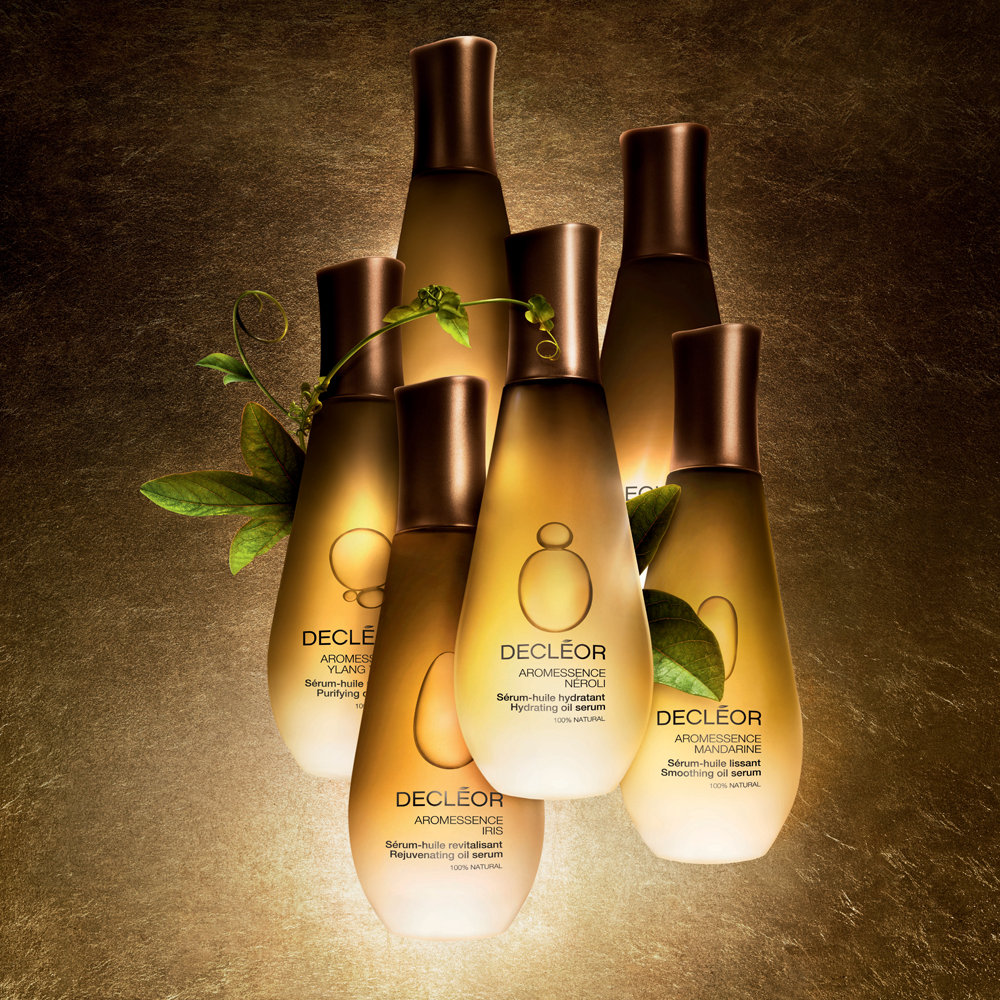 A group od Decleor beauty products arranged against a grainy brown background in gold bottles and leaves emerging from between them